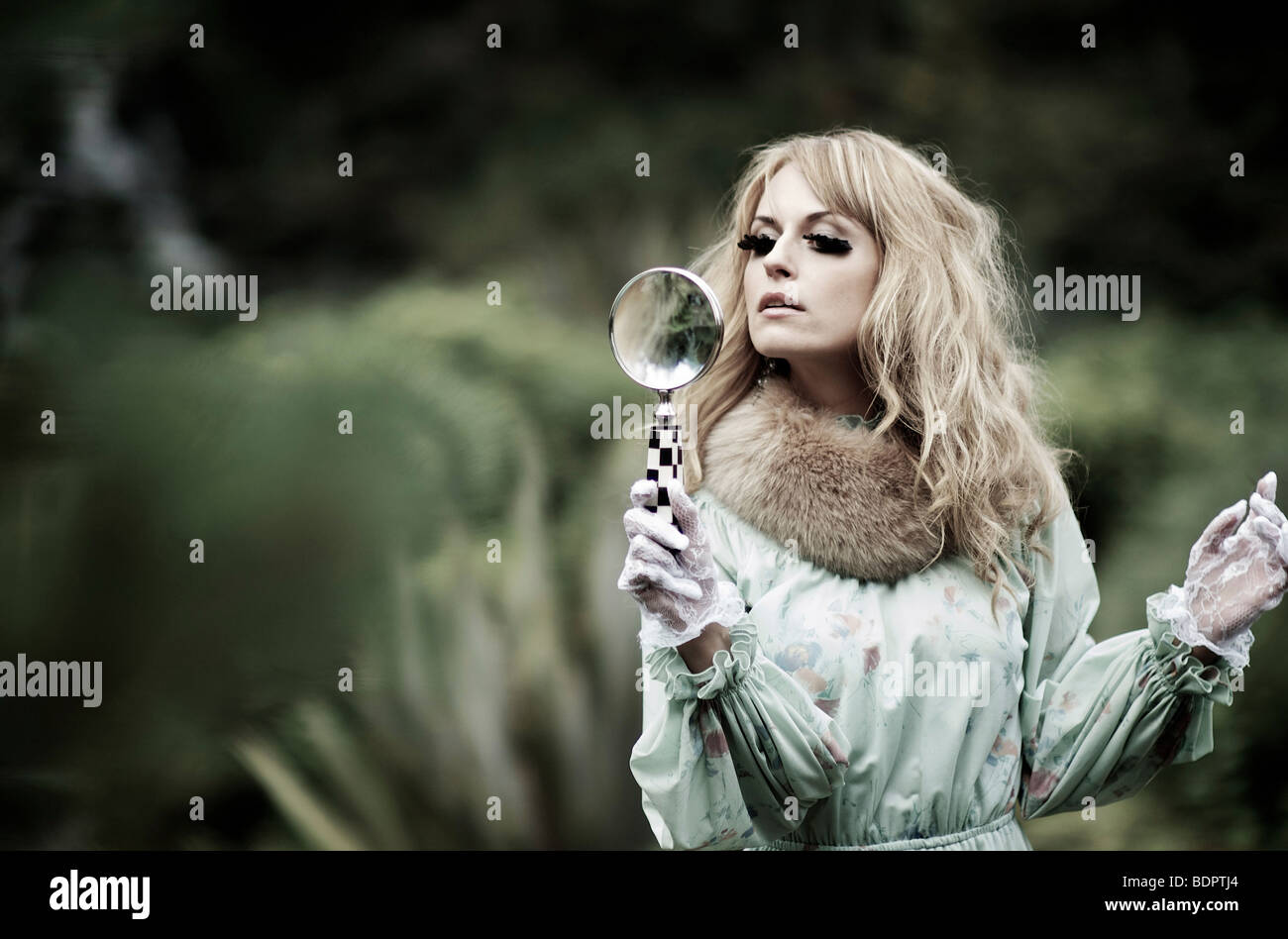 Young female with blonde hair holding a magnifying glass outdoors - Stock Image