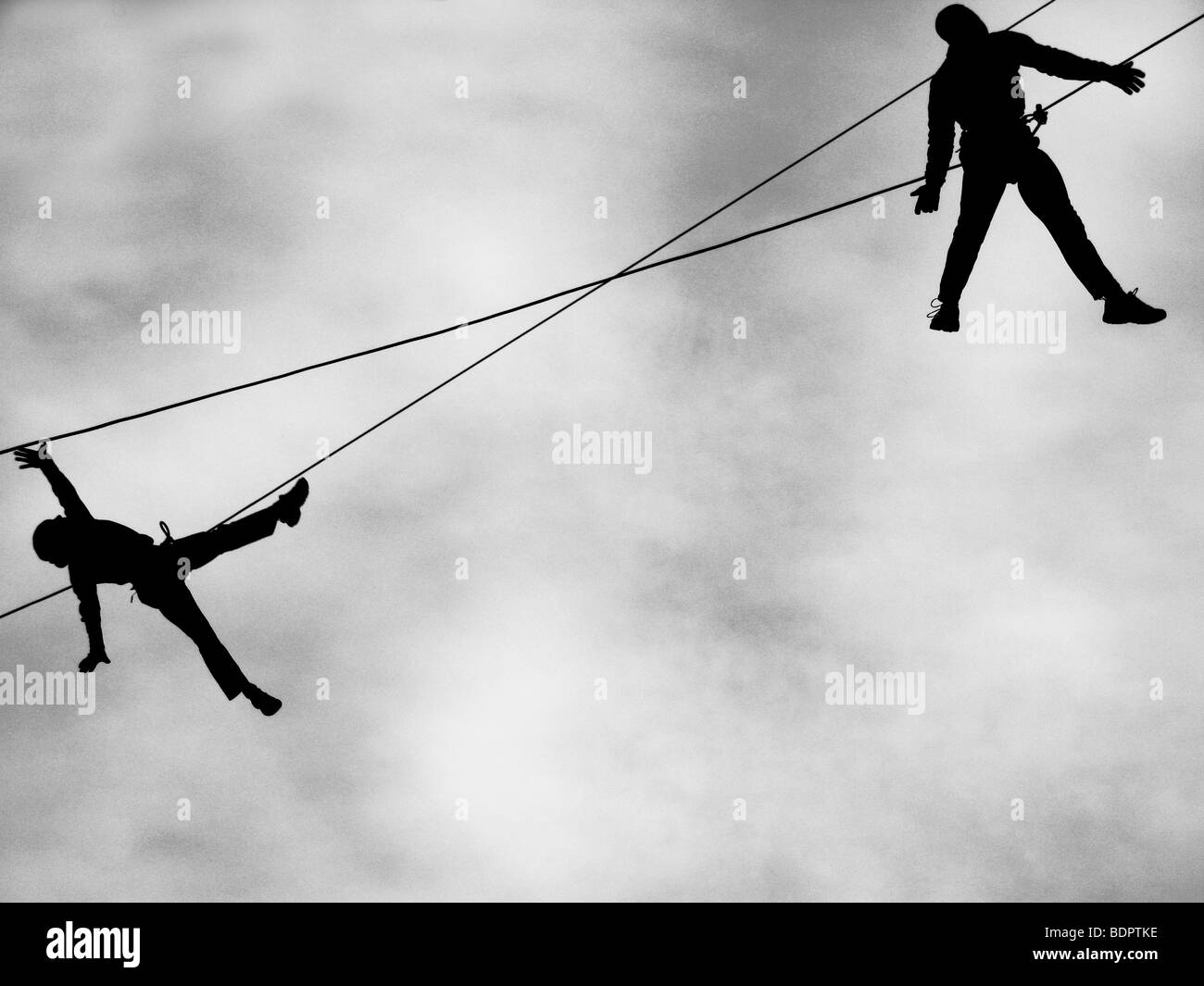 Two figures suspended from high wires - Stock Image