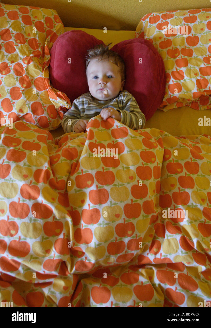 Baby in bed - Stock Image