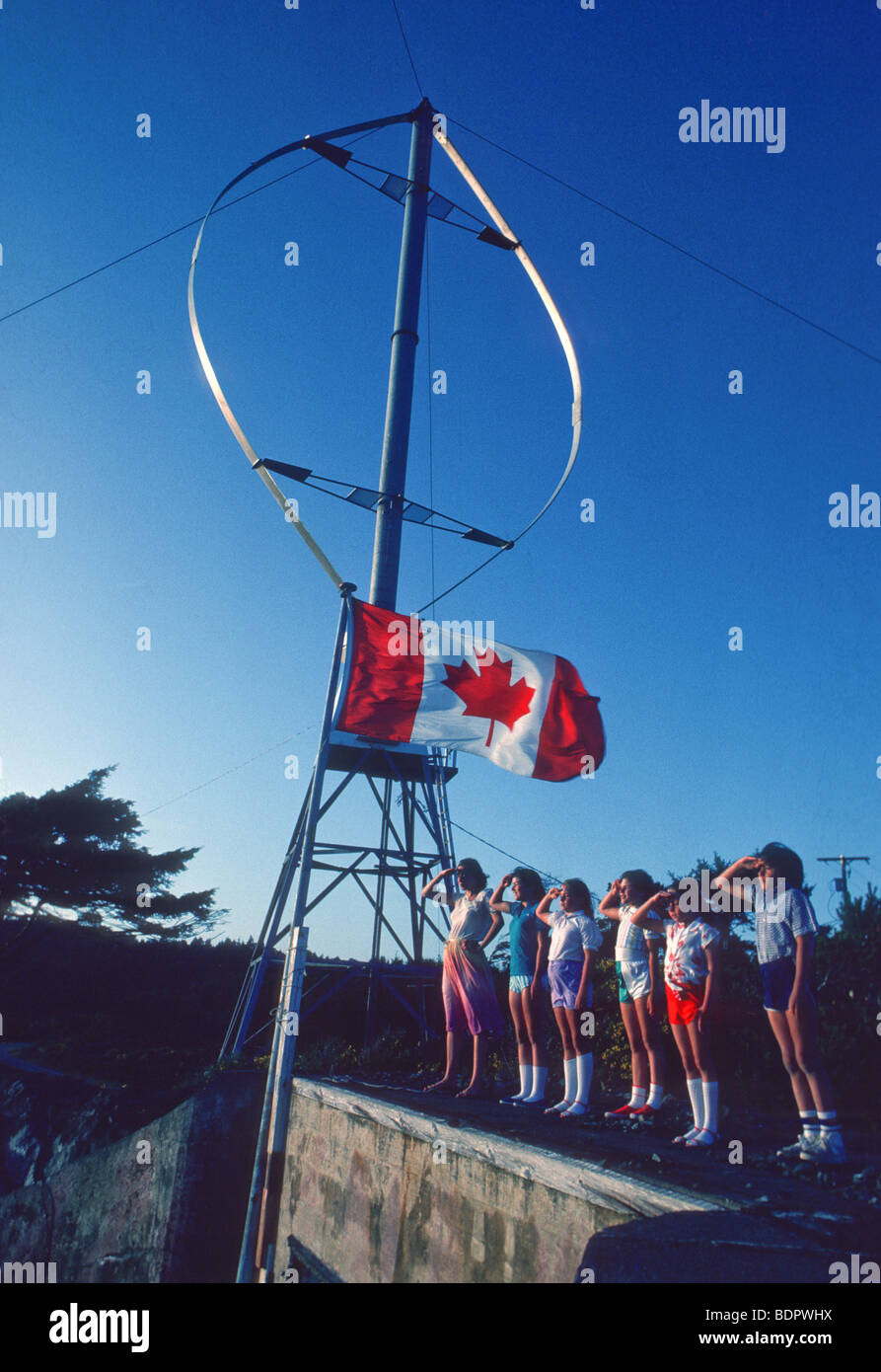Children salute Canadian flag in front of wind turbine - Stock Image