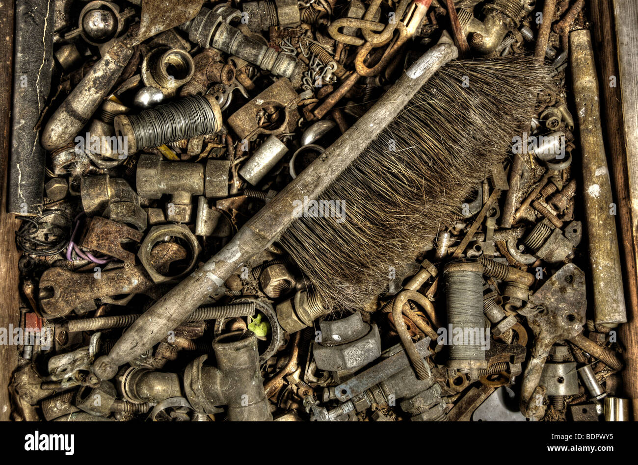 An old hand brush in a box of old nuts and bolts Stock Photo