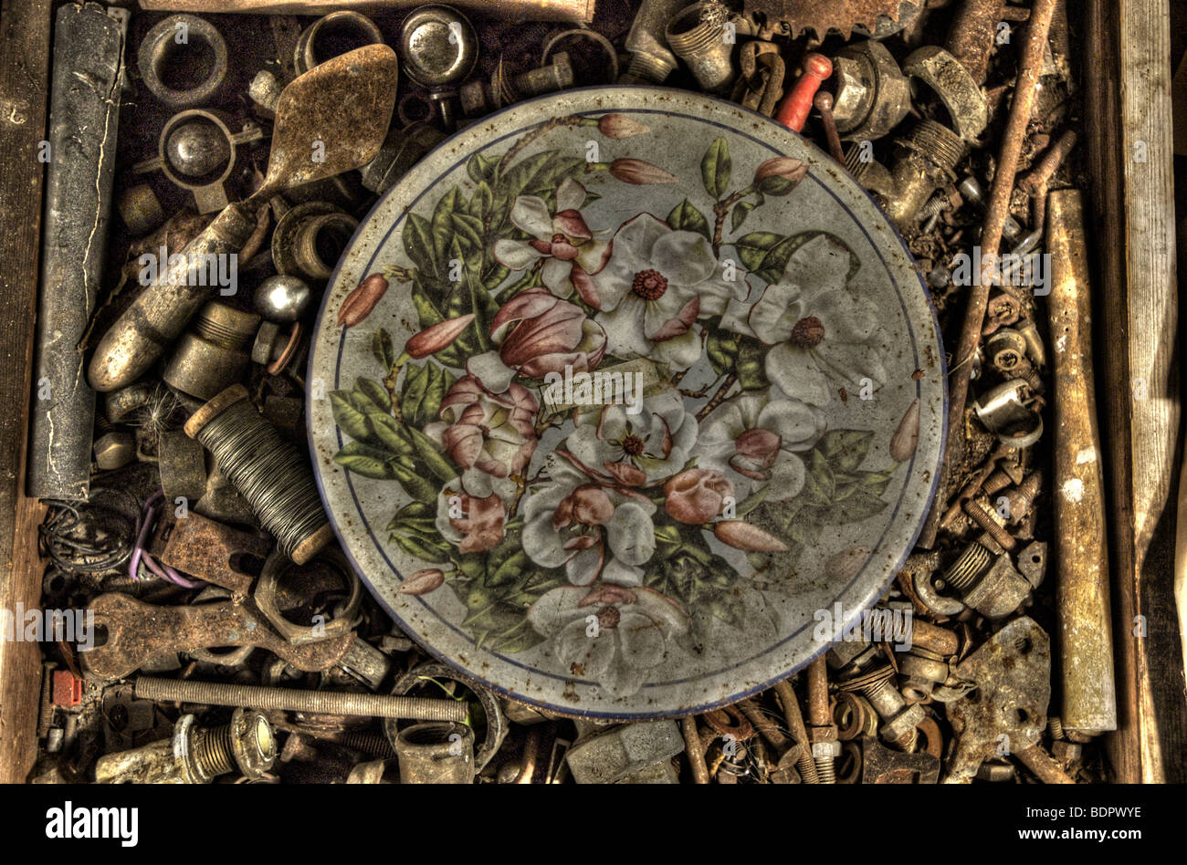 An old tin with a decorative floral design in a box of old nuts and bolts Stock Photo