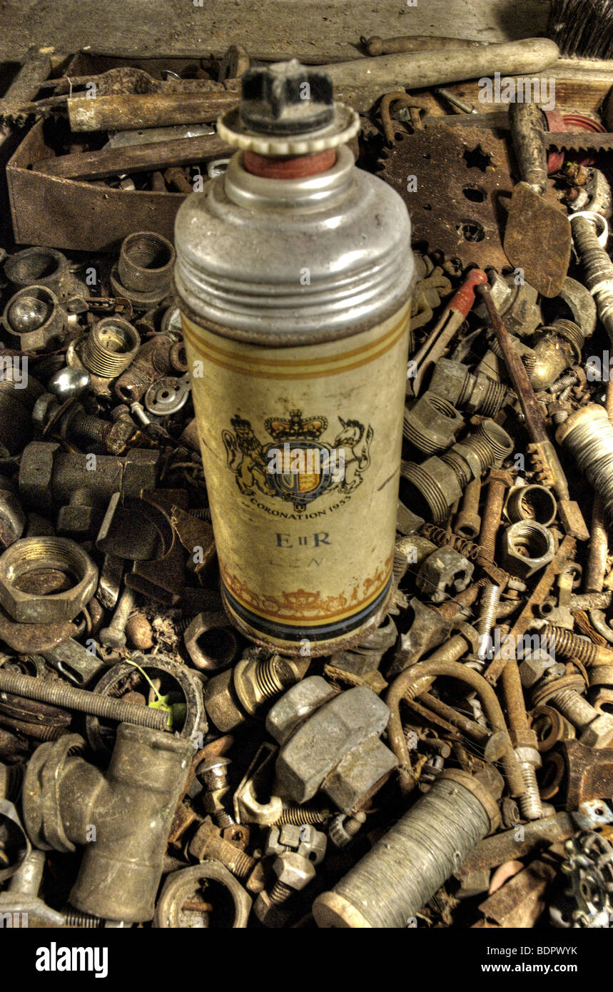 An old thermos flask in a box of old nuts and bolts Stock Photo