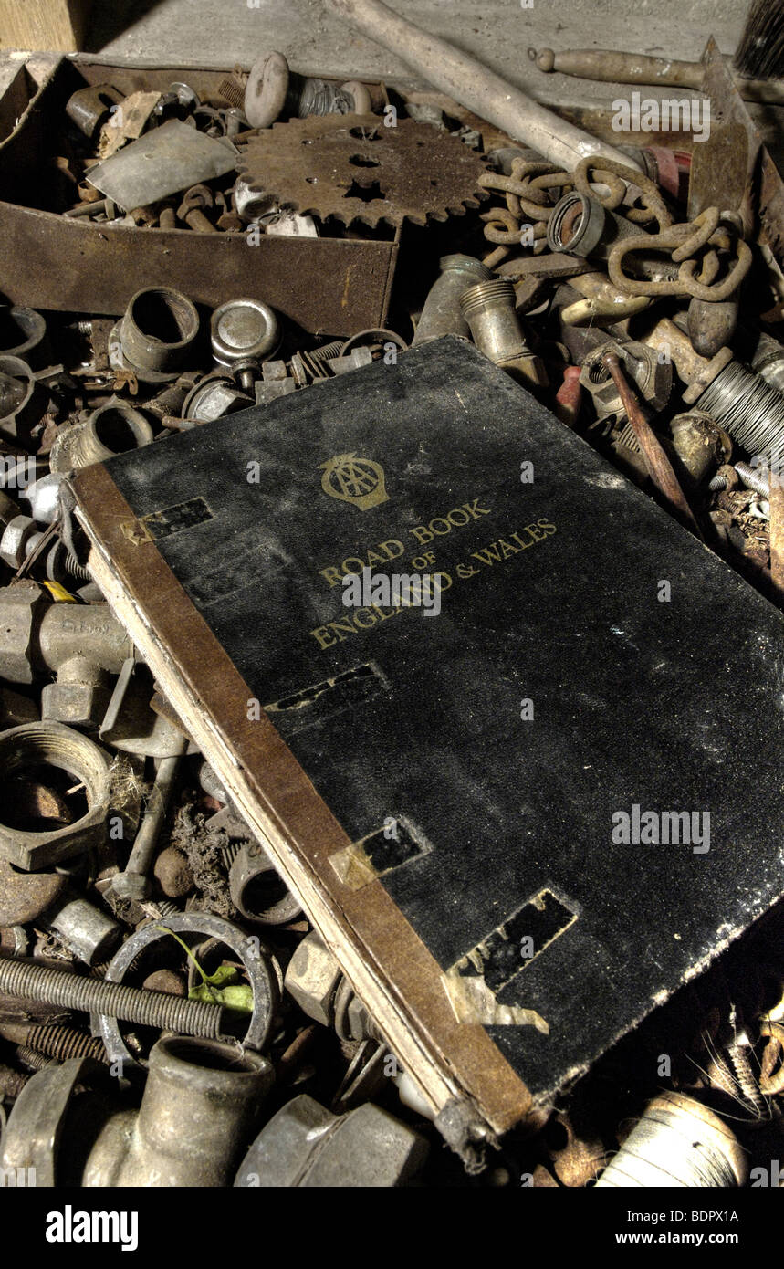 An old black book of AA road maps in a box of old nuts and bolts Stock Photo