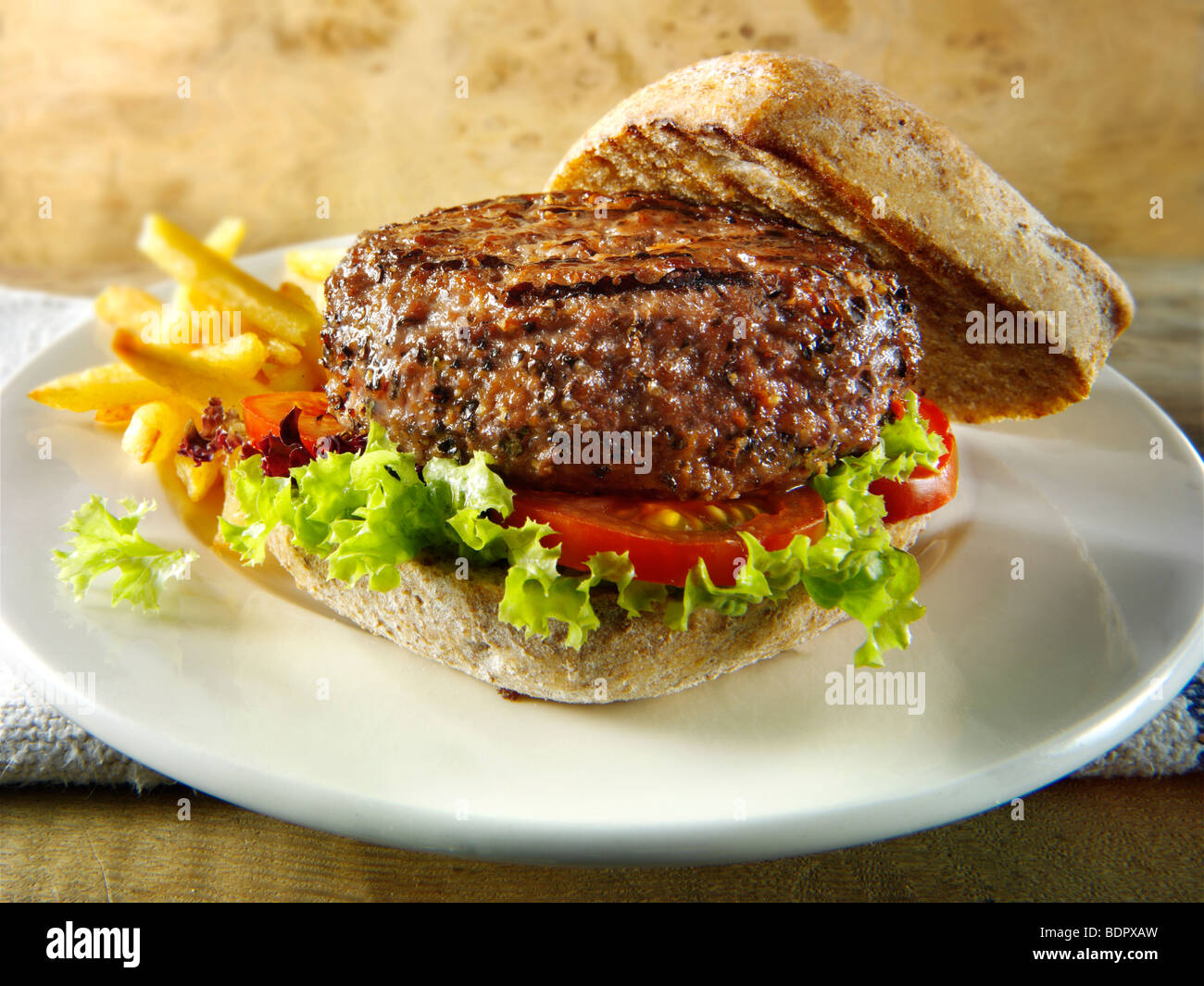 Peppered beef burger with chips and wholemeal bun - Stock Image