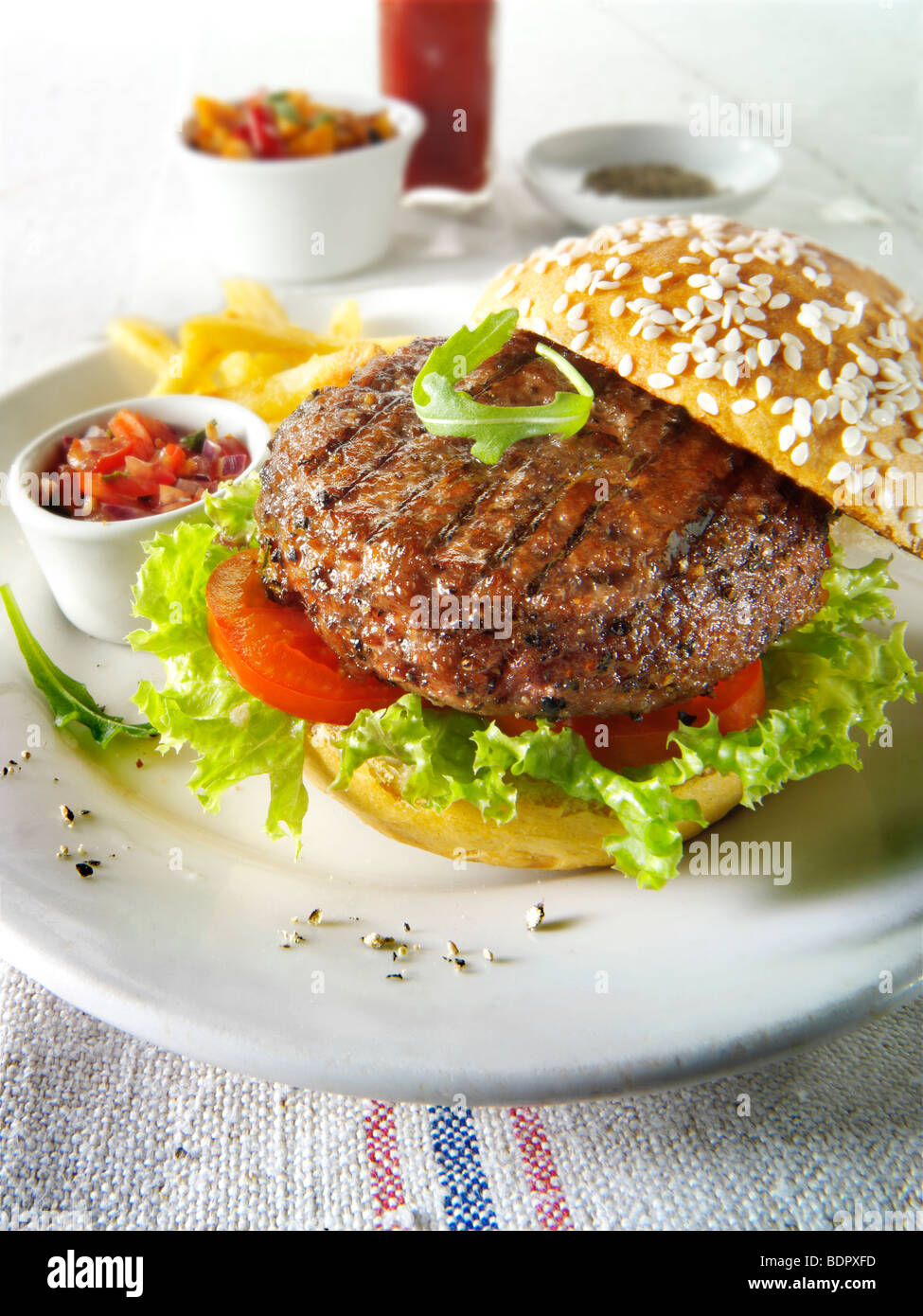 Char grilled beef burger with chips and salad and a seseme bun - Stock Image