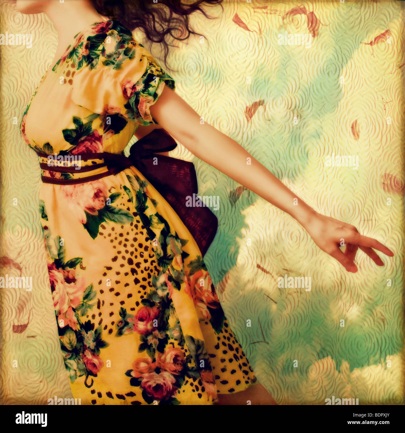 A young woman who appears to be floating against a textured background - Stock Image