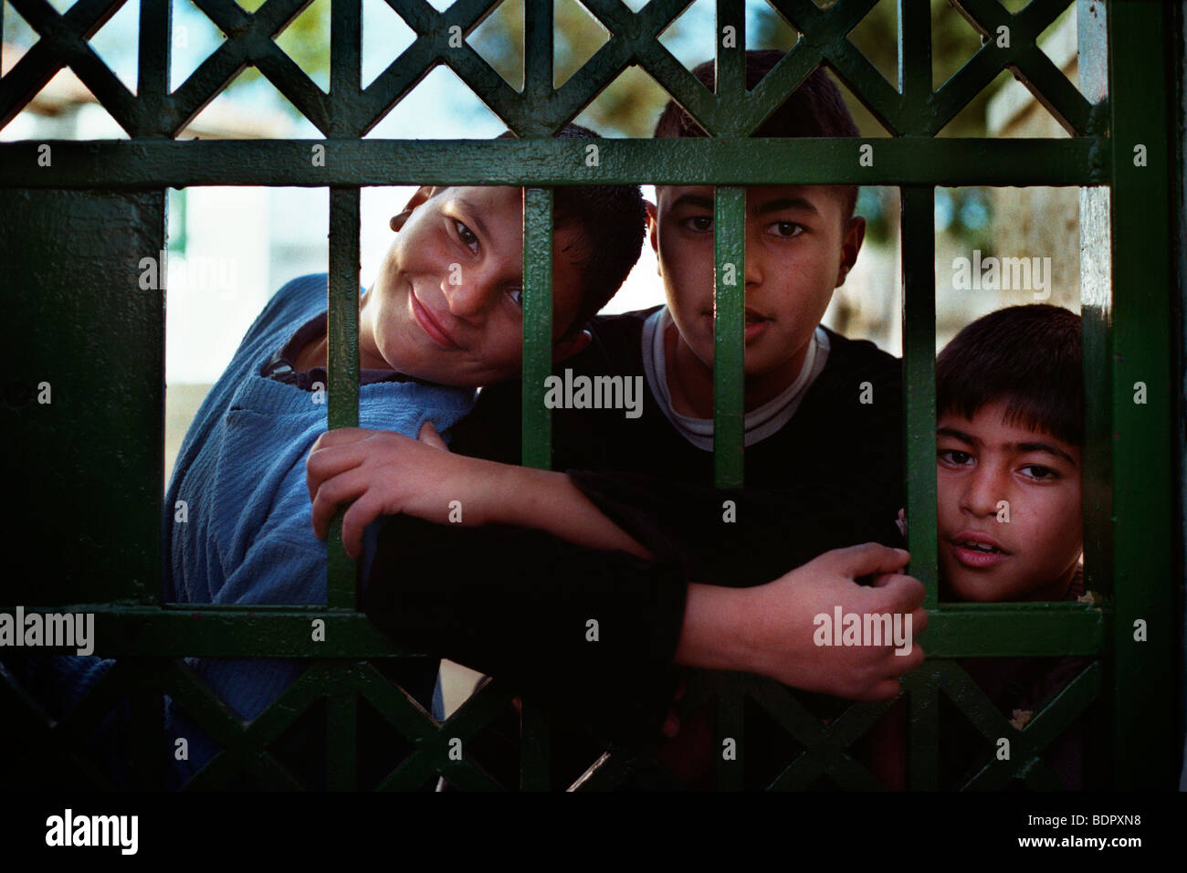 Three palestinian boys behind a grille in Jerusalem - Stock Image