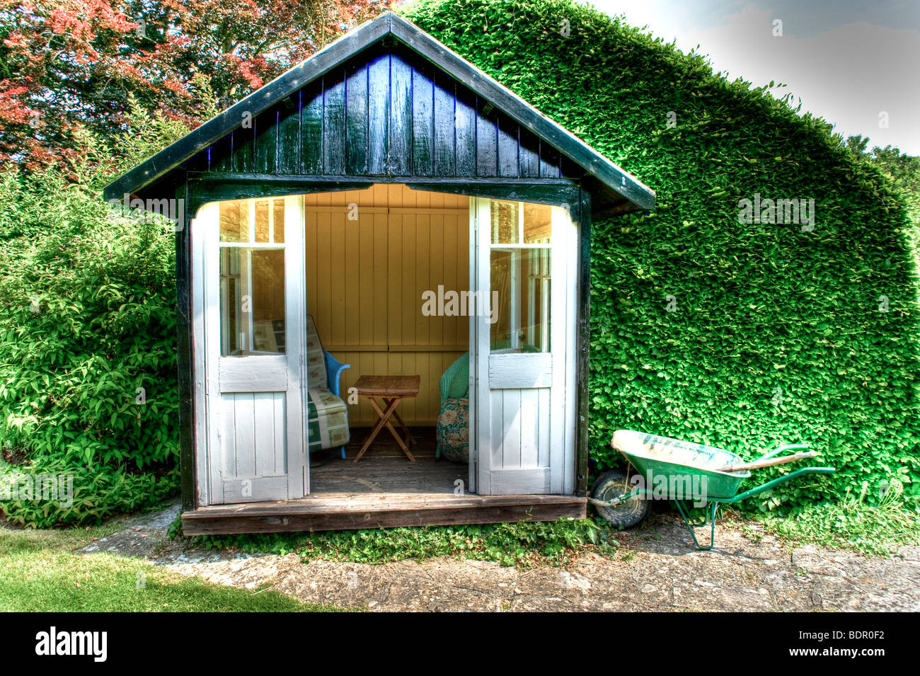 A small wooden summer house with chairs a table and a green wheelbarrow - Stock Image
