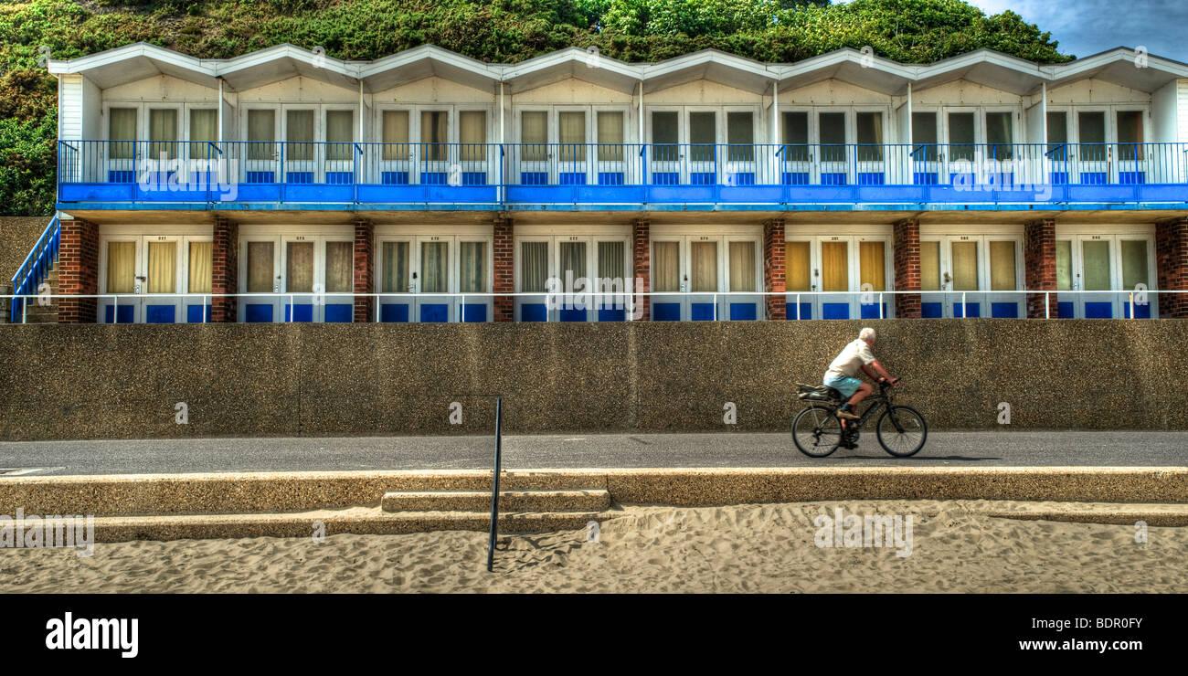 A man riding a bicylce along a sea front - Stock Image