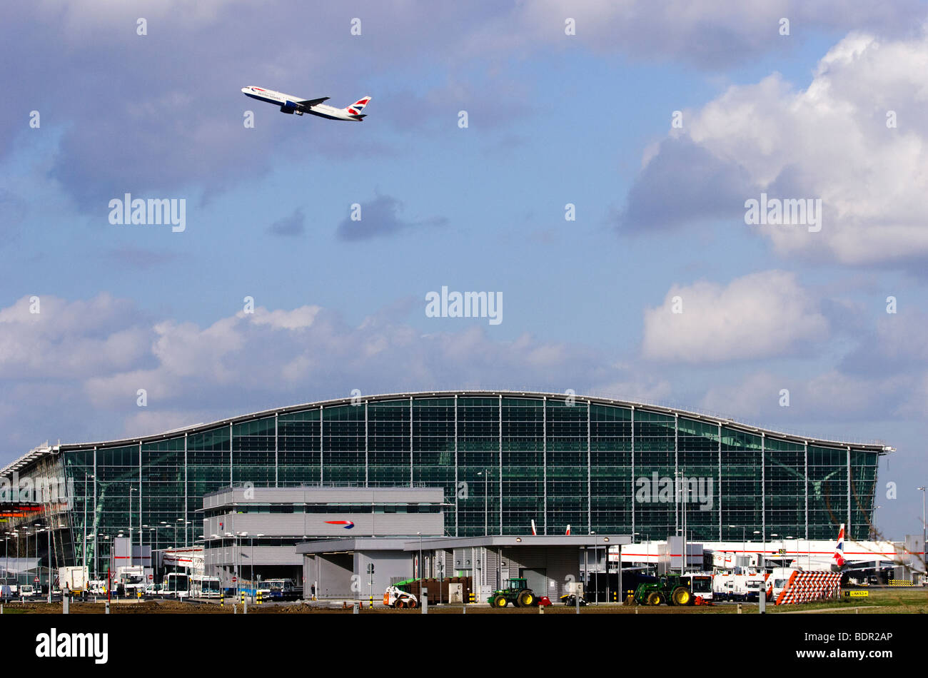 Terminal 5, London Heathrow Airport, with British Airways Boeing 767 taking off in background. - Stock Image