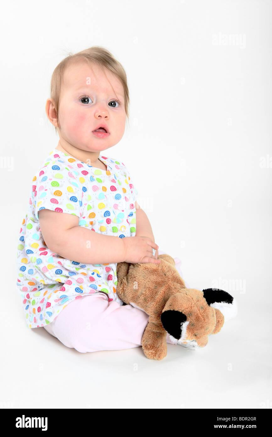 Baby Girl on sitting white backdrop with stuffed animal - Stock Image