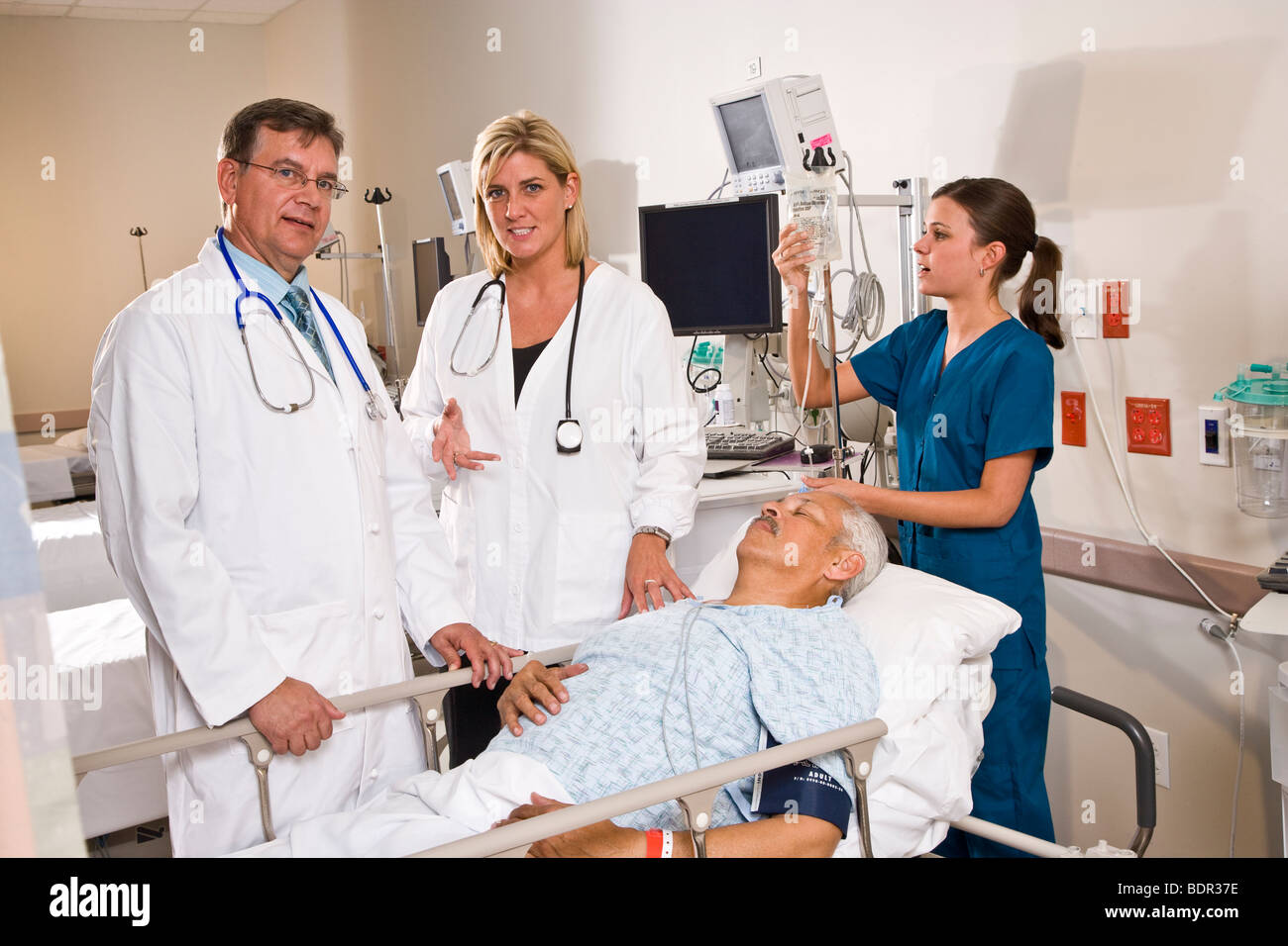 doctors and nurse in hospital recovery room with patient