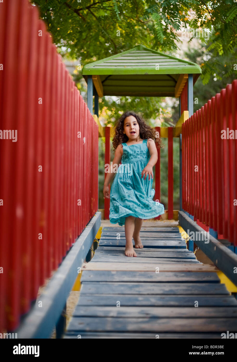 girl runing on a wooden 'bridge' in a playground - Stock Image