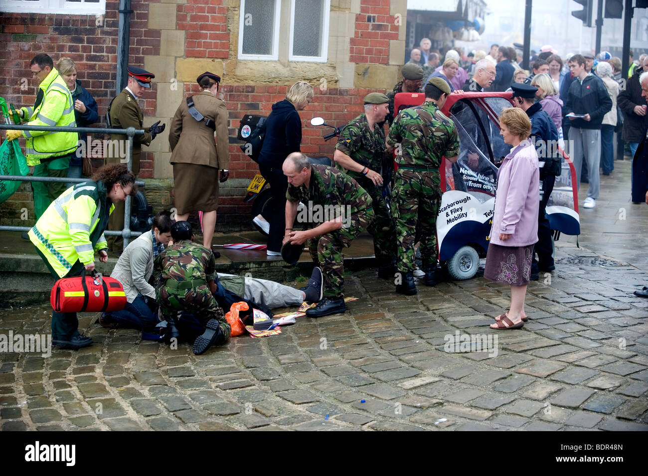 An elderly man is treated by emergency services and the armed forces after his mobility scooter toppled over. Stock Photo