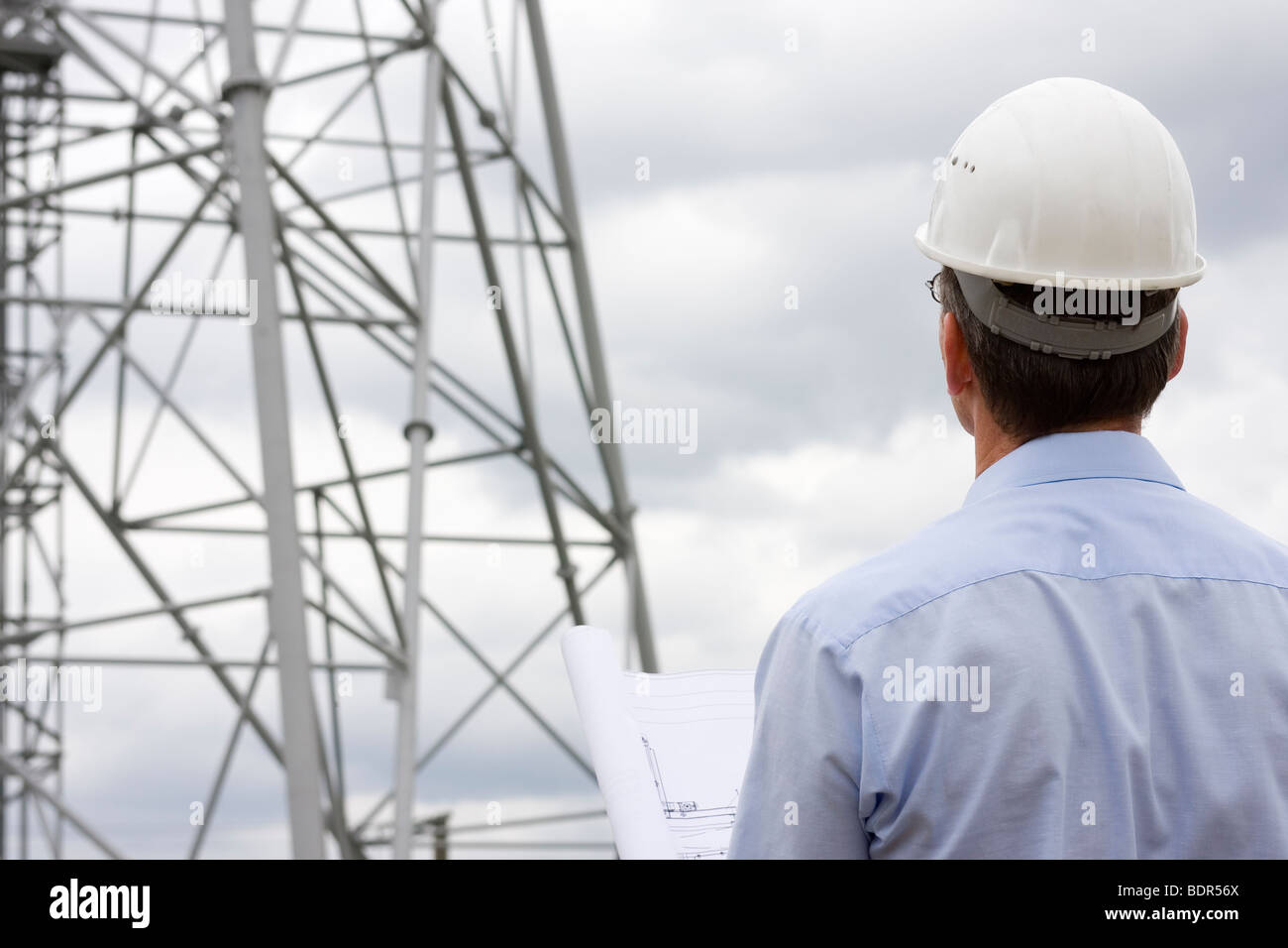 Engineer looking at construction side with plan in his hand - Stock Image