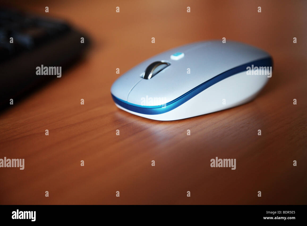 blue computer mouse on the wooden table closeup - Stock Image