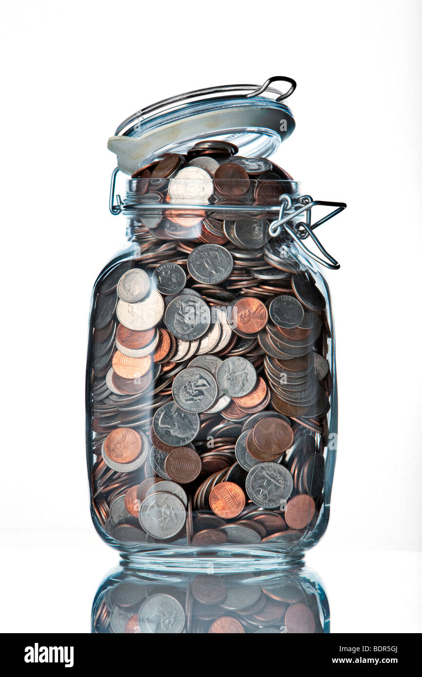 jar of coins on a white background - Stock Image