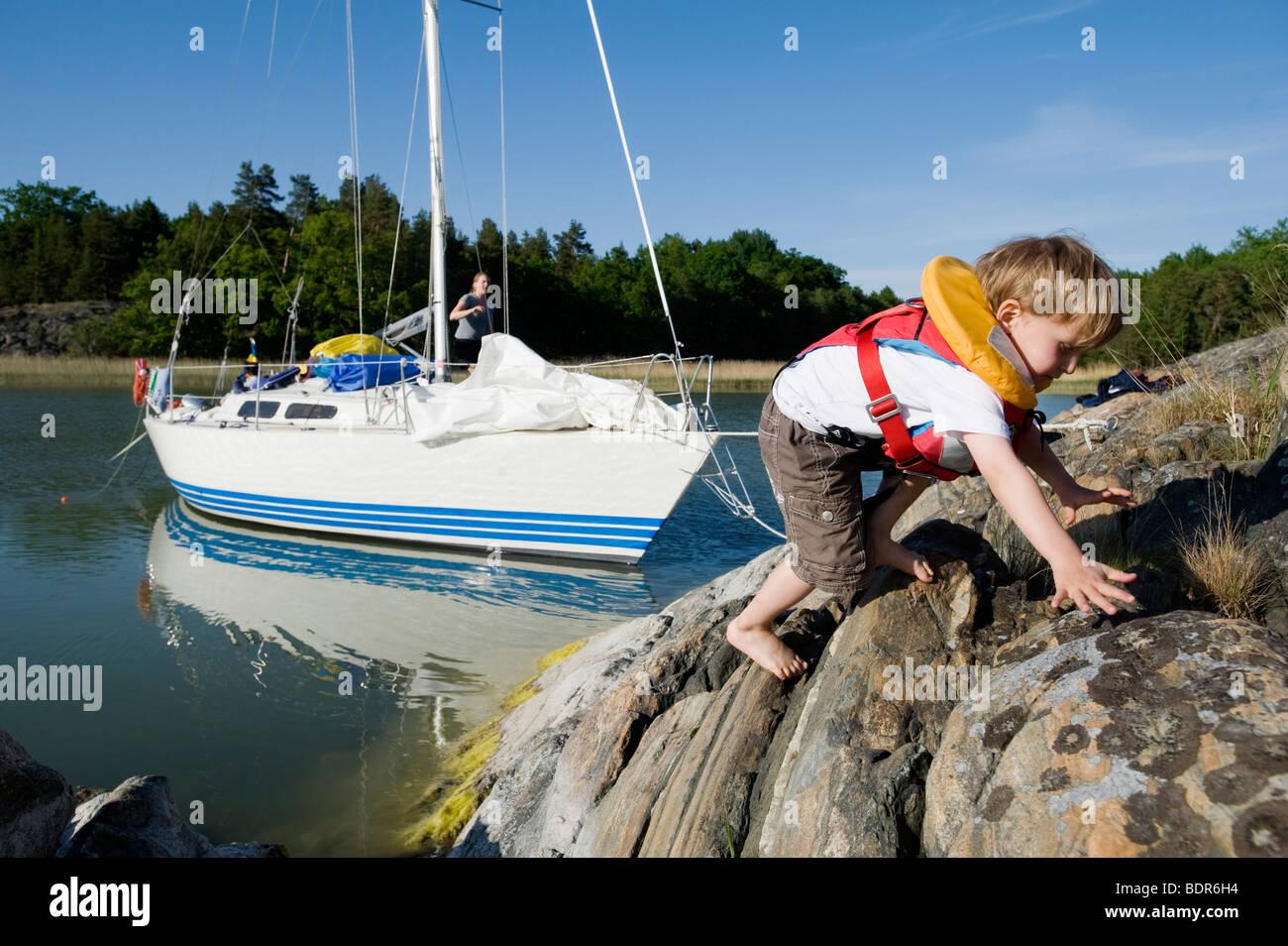 A boy climbing on a cliff Sweden. - Stock Image