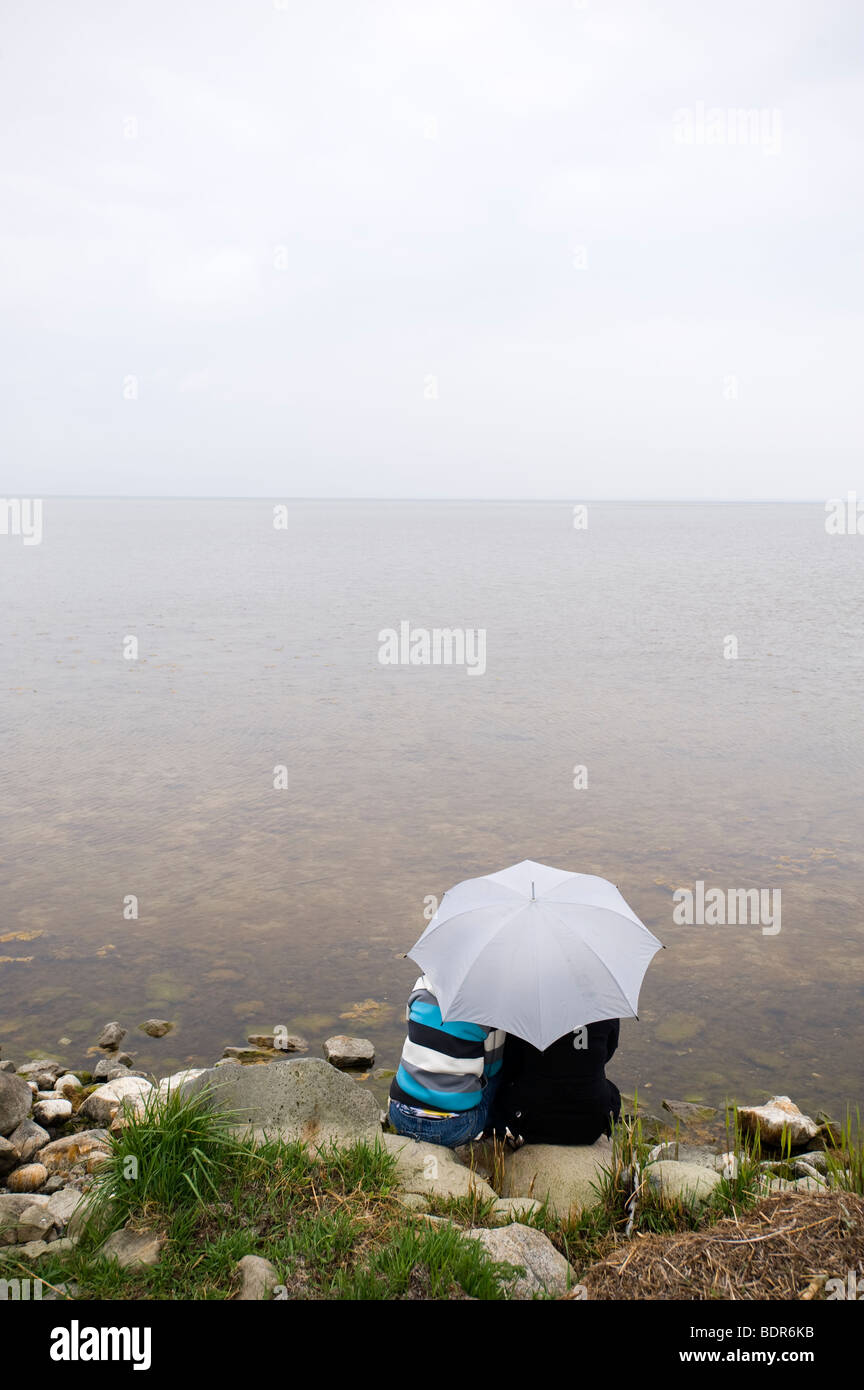 Two persons sitting under an umbrella Sweden. - Stock Image