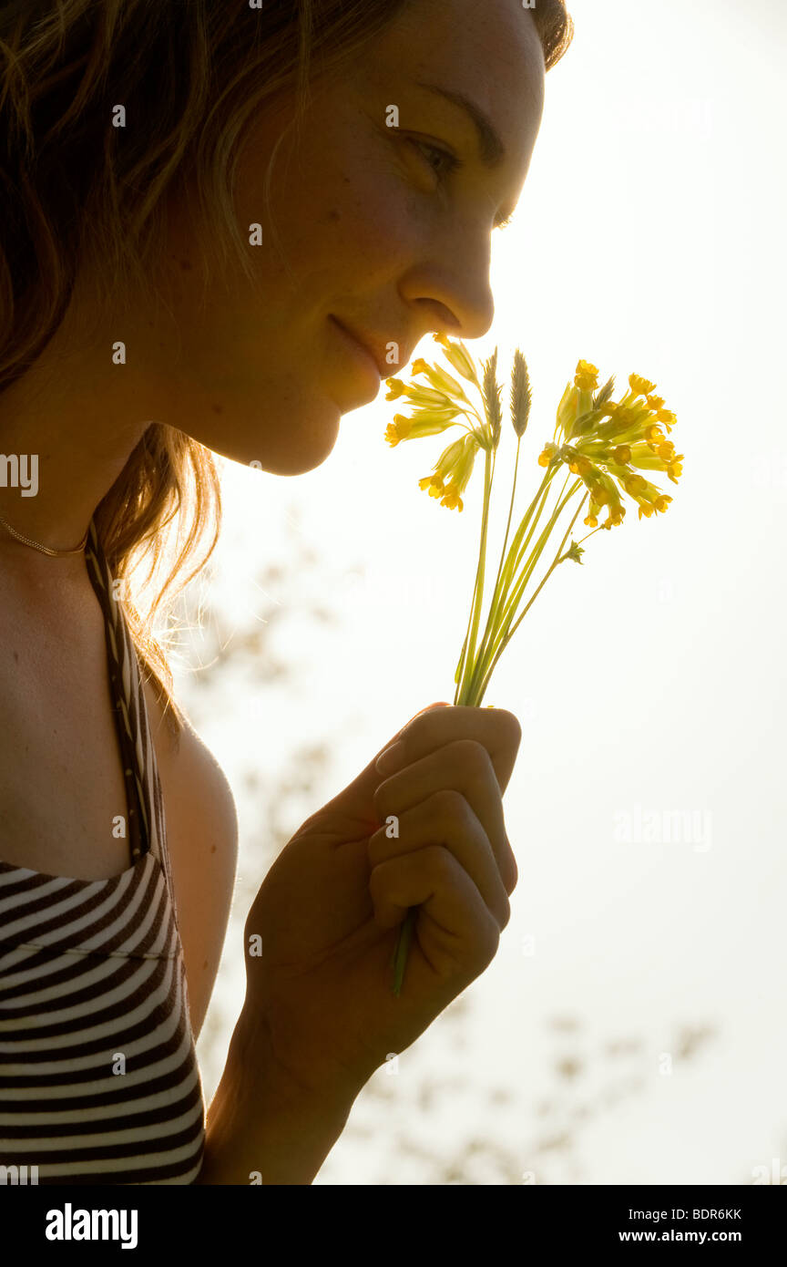 Portrait of s woman smelling a flower. - Stock Image