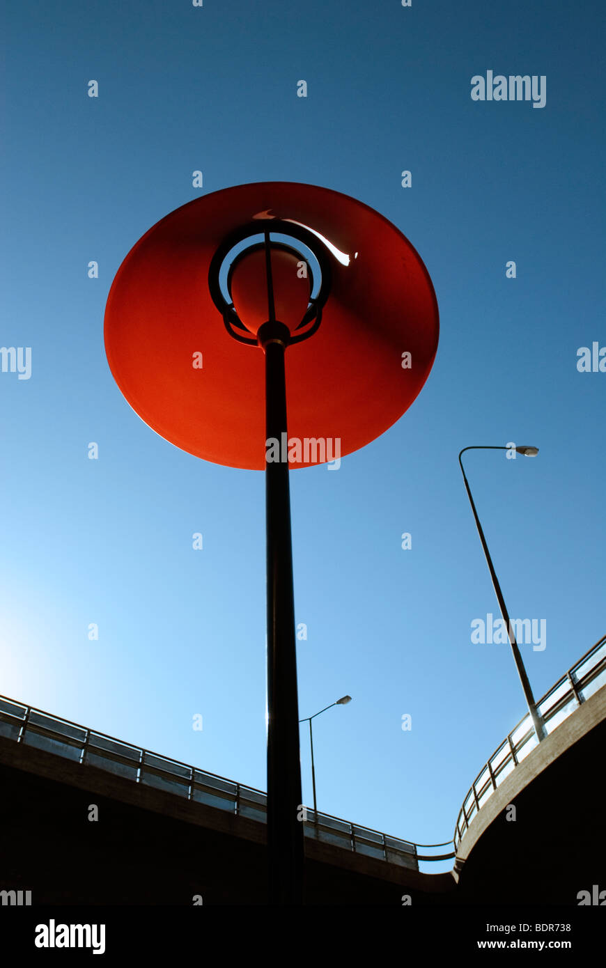 A red outdoor lamp by a viaduct Stockholm Sweden. - Stock Image