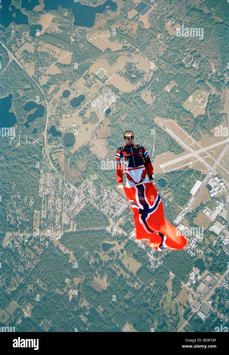 A parachute jumper holding a Norwegian flag USA. - Stock Image