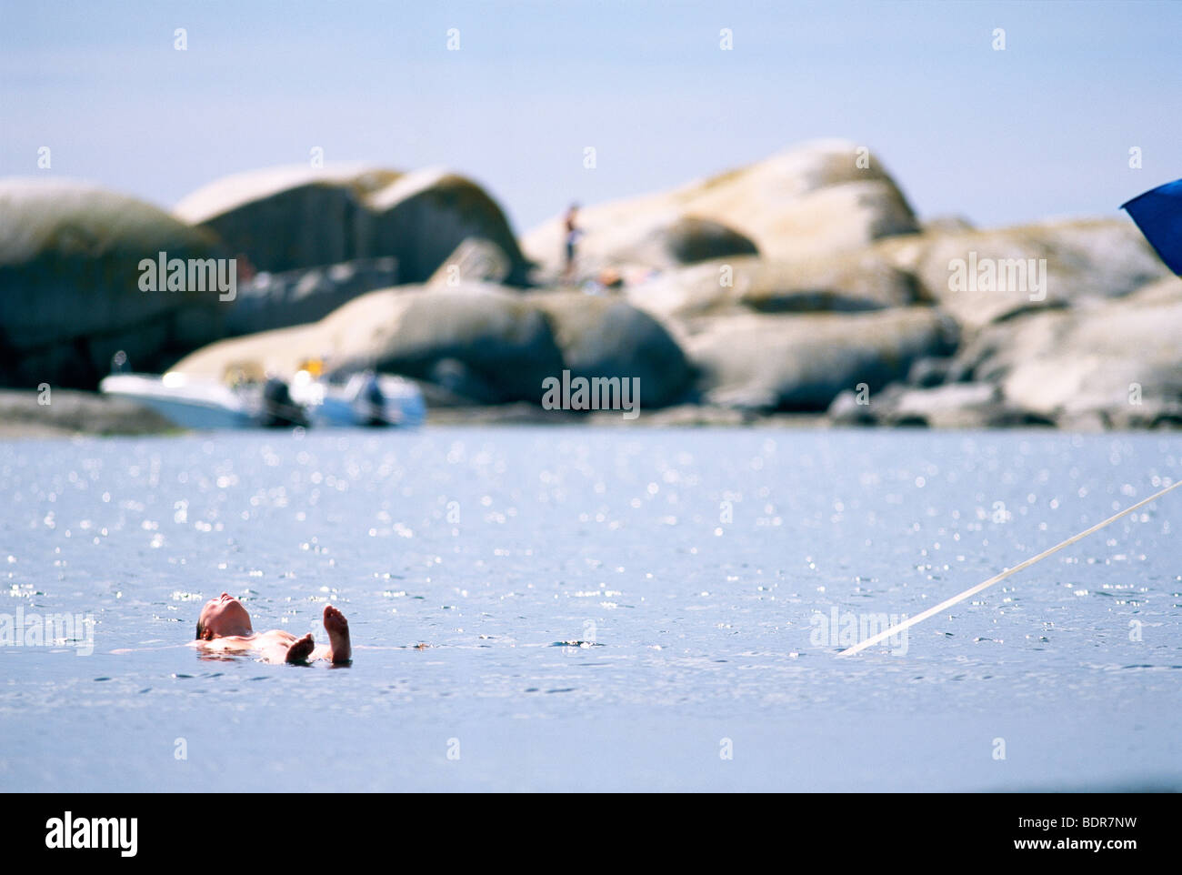 A woman swimming in the ocean, Vastkusten, Sweden. - Stock Image
