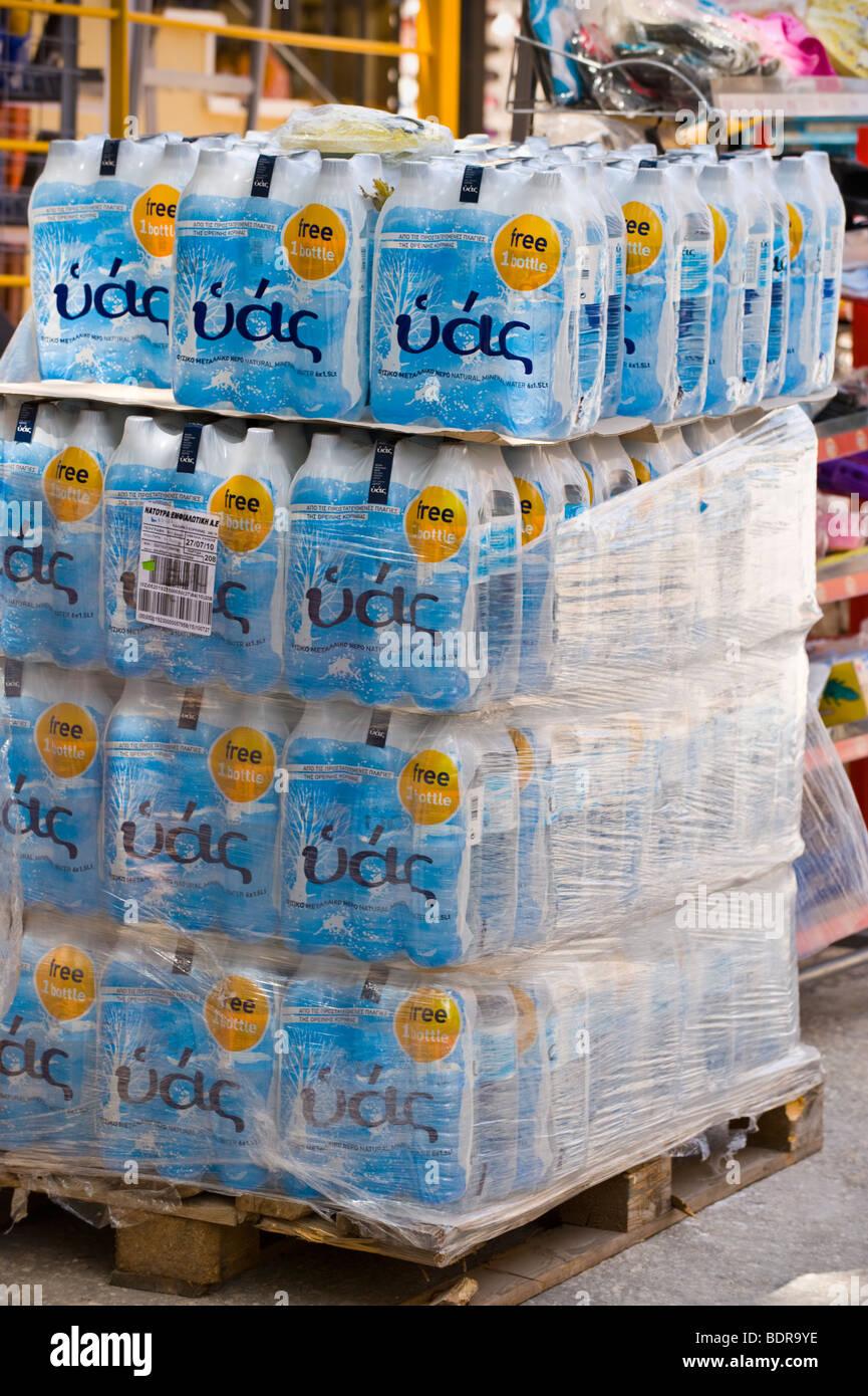 Pallet stack of bottled water outside shop in village of Fiskardo on the Greek Mediterranean island of Kefalonia - Stock Image