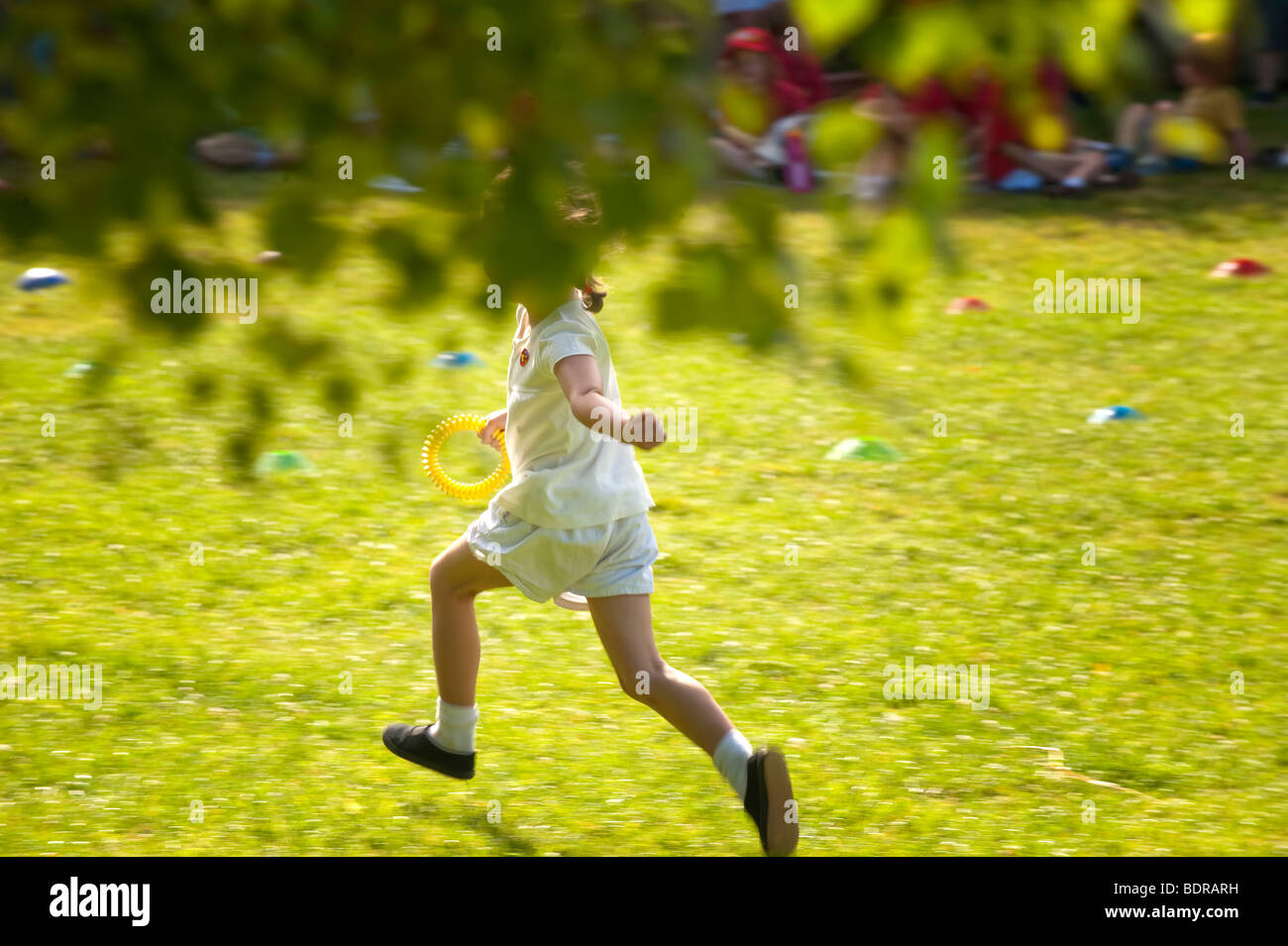 Child running in relay race at primary school sports day - Stock Image