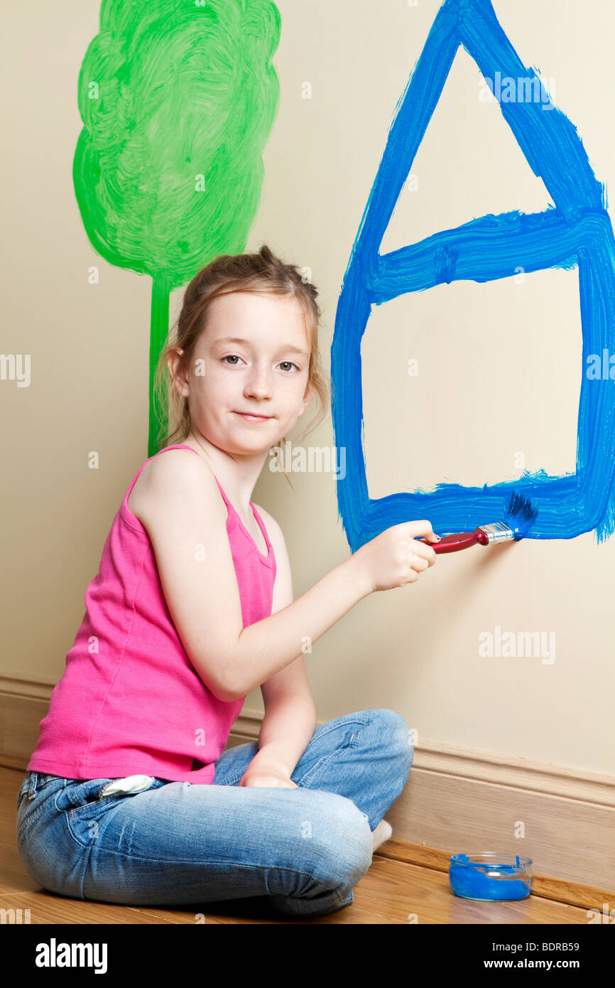 Young child painting on a wall - Stock Image