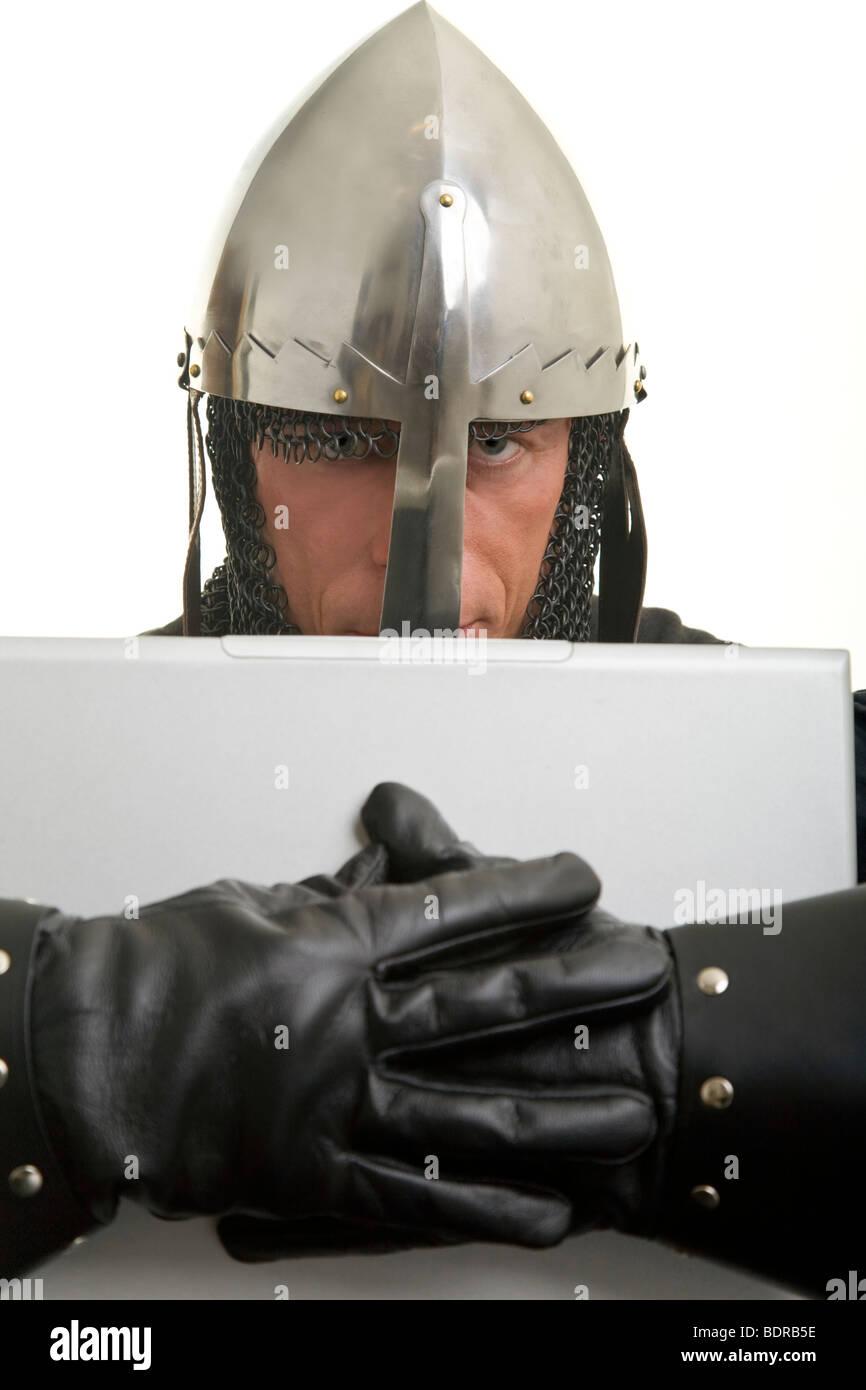 Tempelritter mit Nasalhelm und Lederhandschuhen umarmt einen Laptop Stock Photo