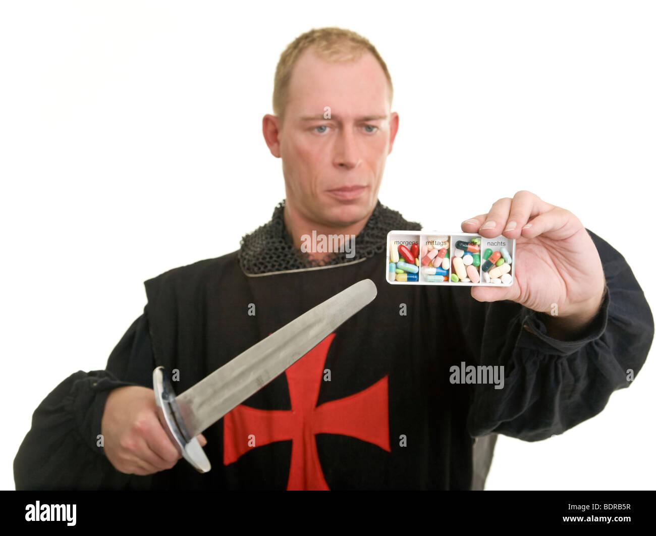 knight with knife and drugs, Darsteller eines Tempelritters richtet seinen Dolch auf eine Pillendose Stock Photo