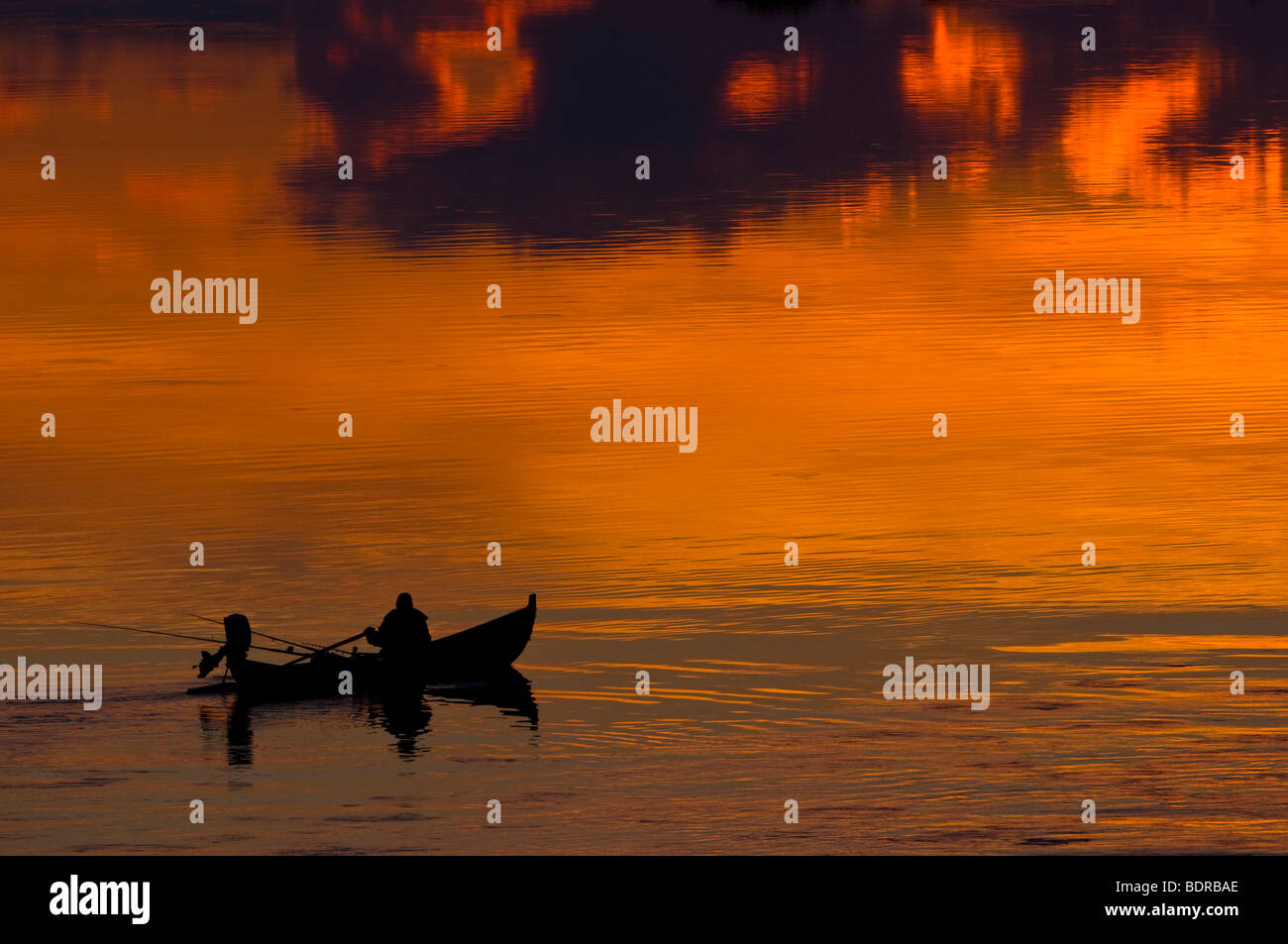 angler in boat on torne river at afterglow, lapland, sweden - Stock Image