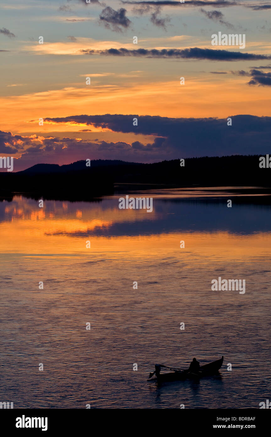 angler in boat on torne river at afterglow, lapland, sweden Stock Photo