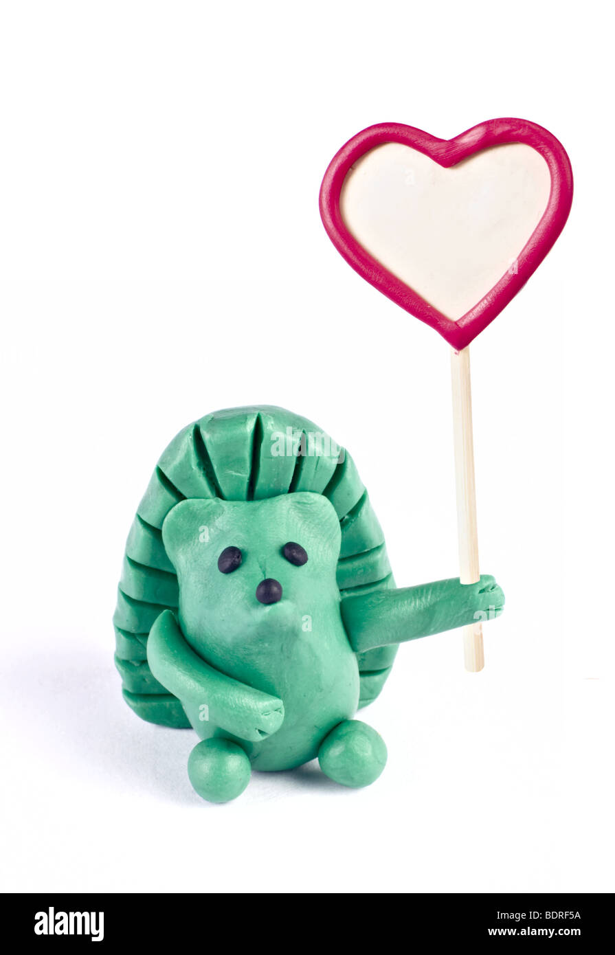 Plasticine hedgehog retaining heart-shaped banner Stock Photo