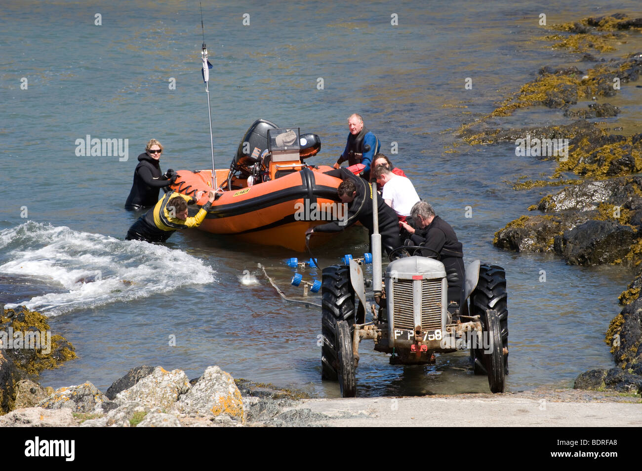 Using a tractor to haul a boat out of the sea on a slipway in Wales - Stock Image