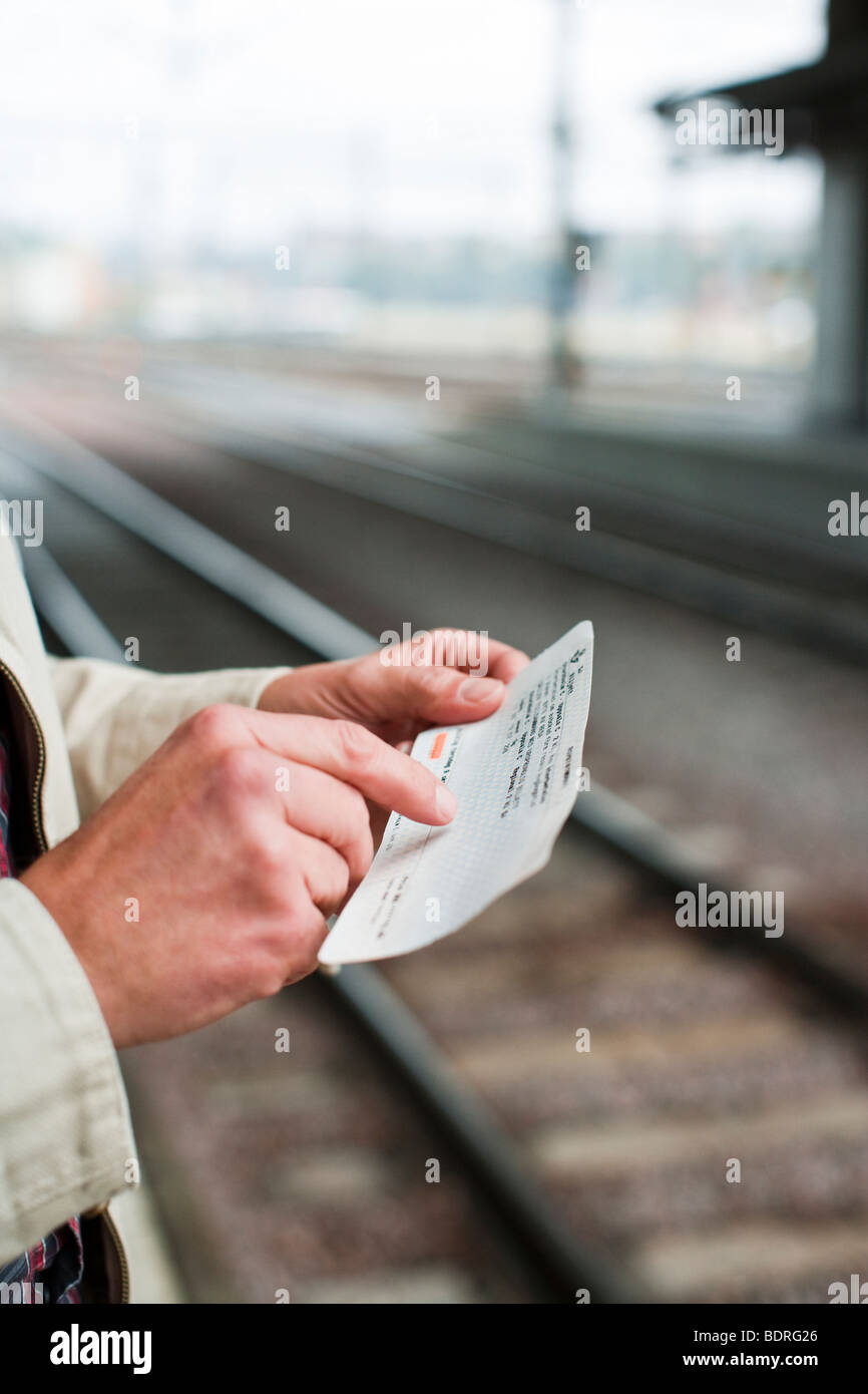 A man at a platform of a railway station - Stock Image