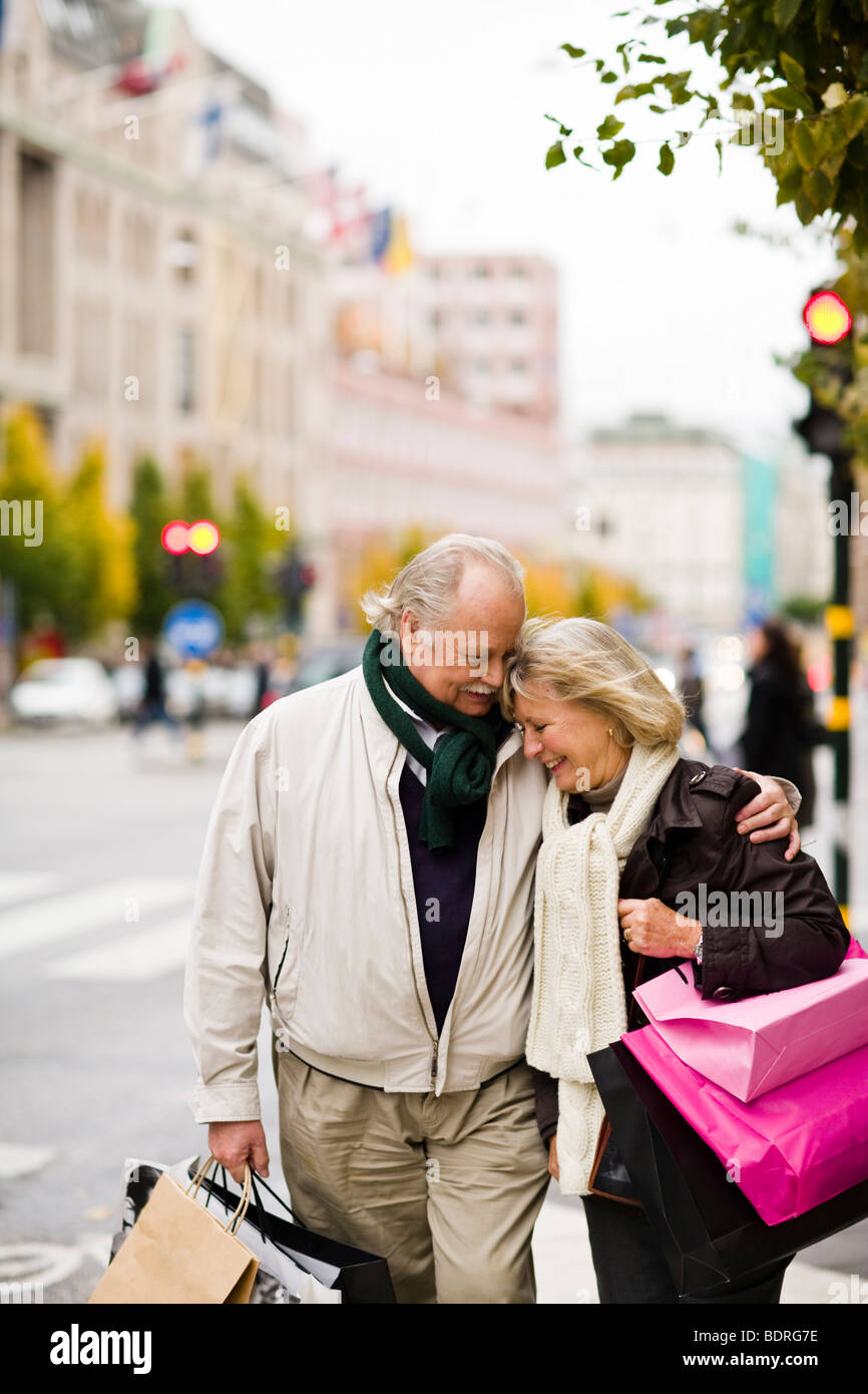 A senior couple carrying shopping bags - Stock Image
