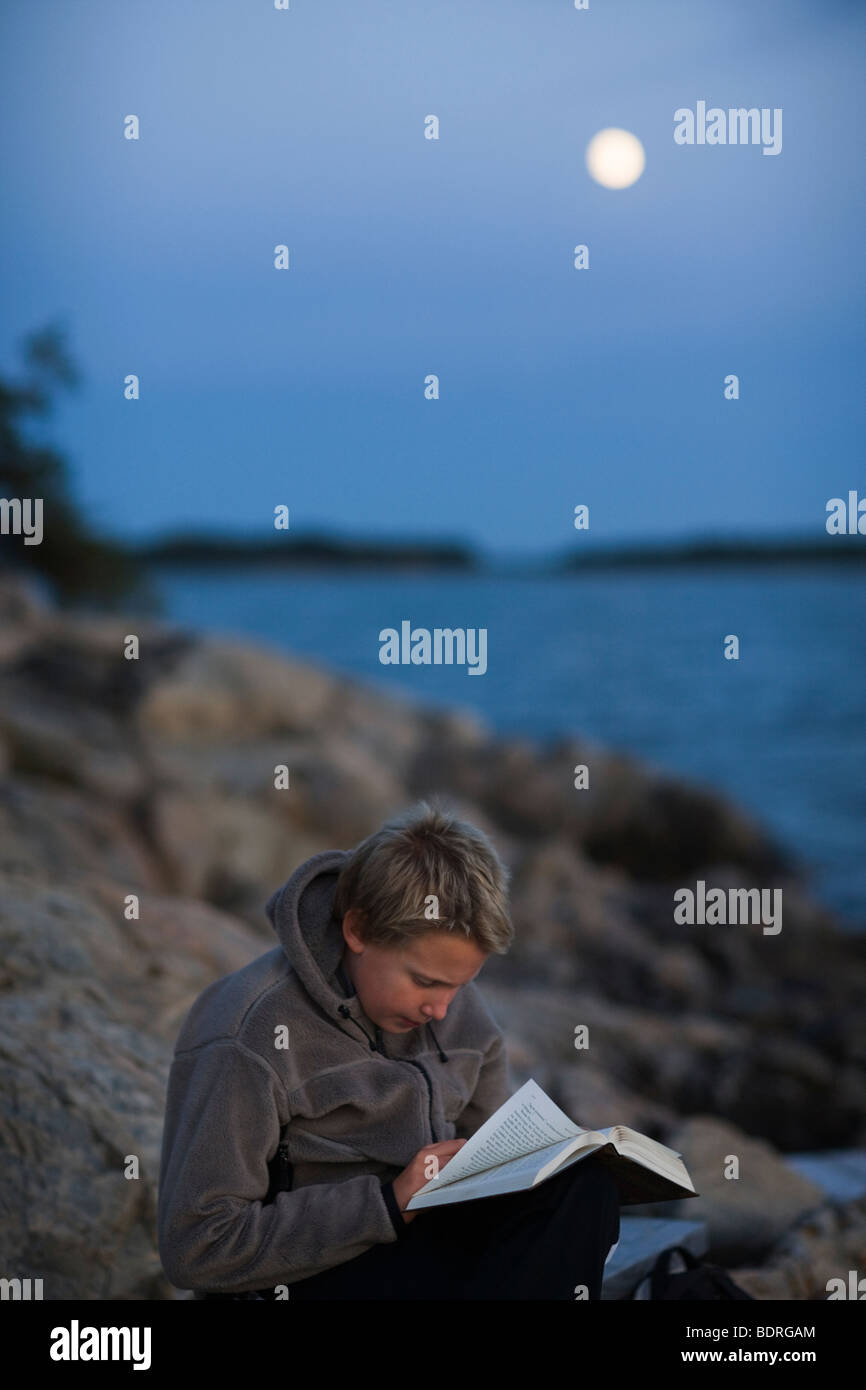 A boy reading by the sea in the moonlight - Stock Image