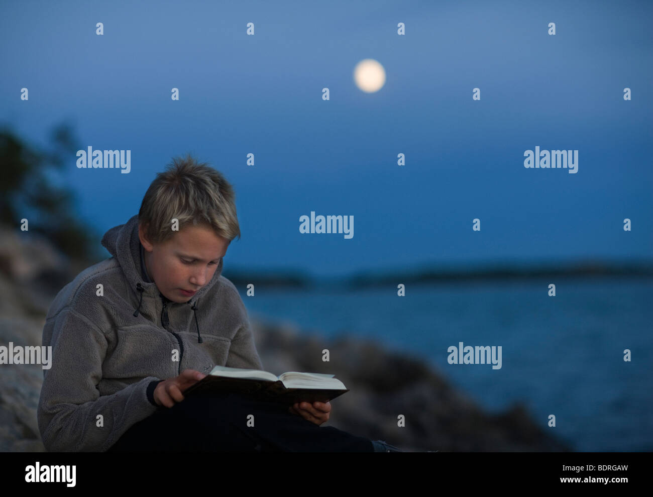 A boy reading a book in the moonlight - Stock Image