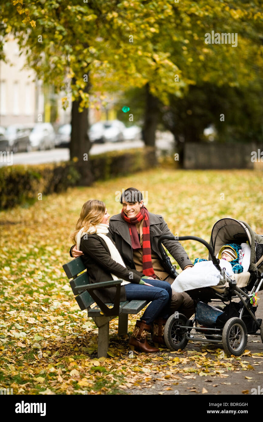 A couple siting with their son in a park - Stock Image