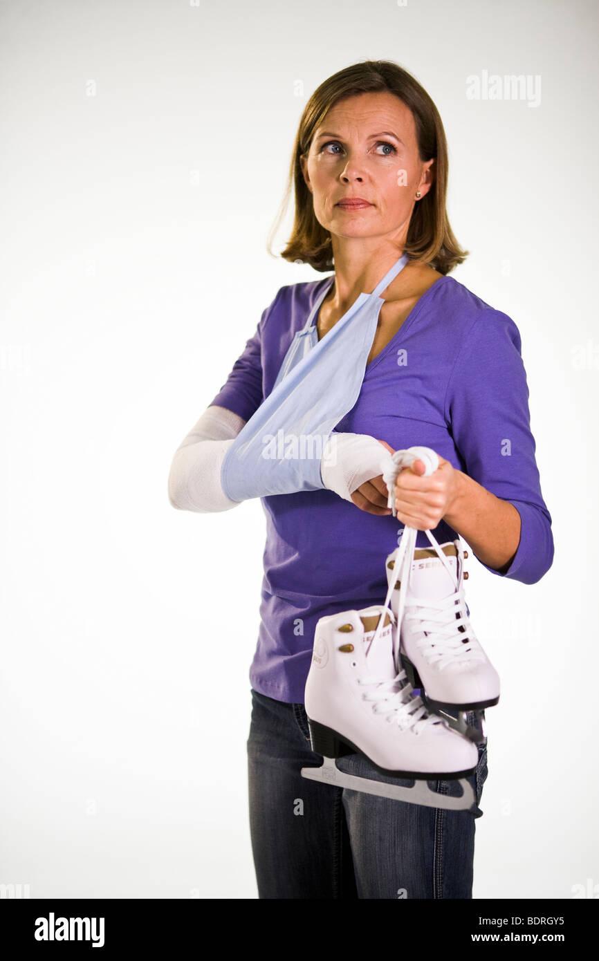 An injured woman holding skates. - Stock Image