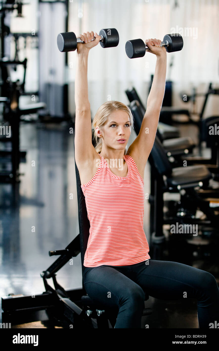 Woman weight training at a gym - Stock Image