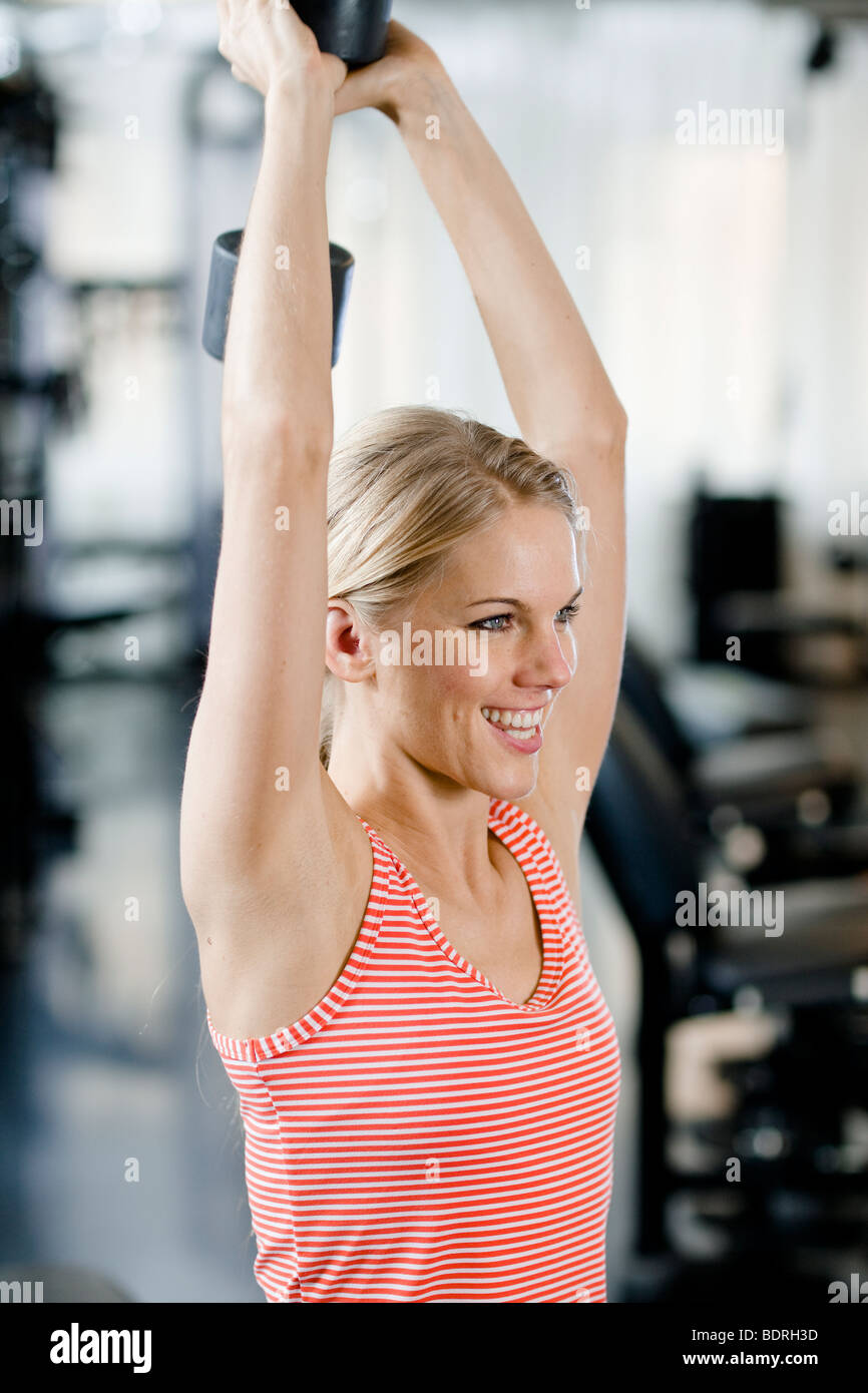 Woman weight training at a gym Stock Photo
