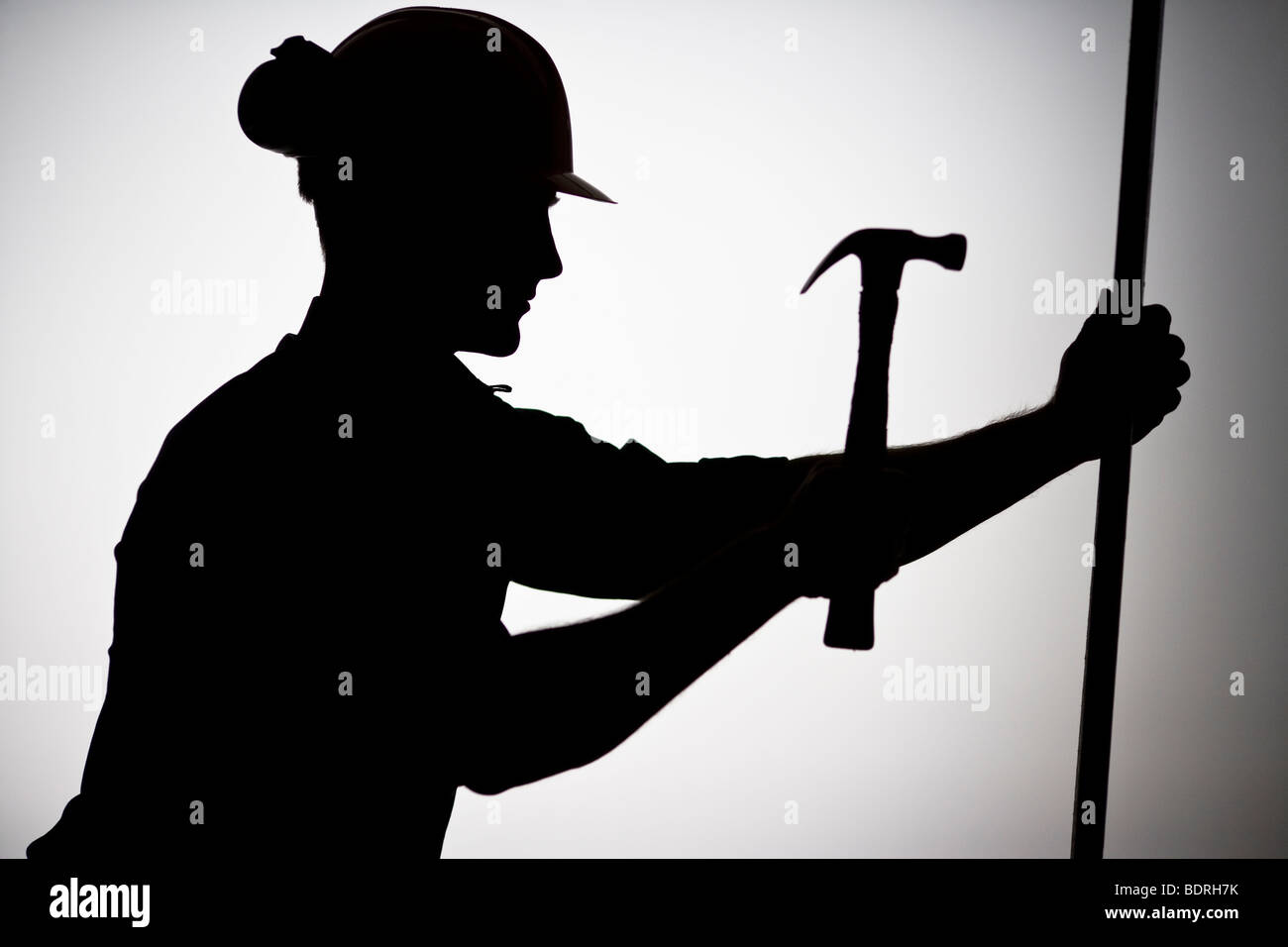 A construction worker using a hammer. - Stock Image