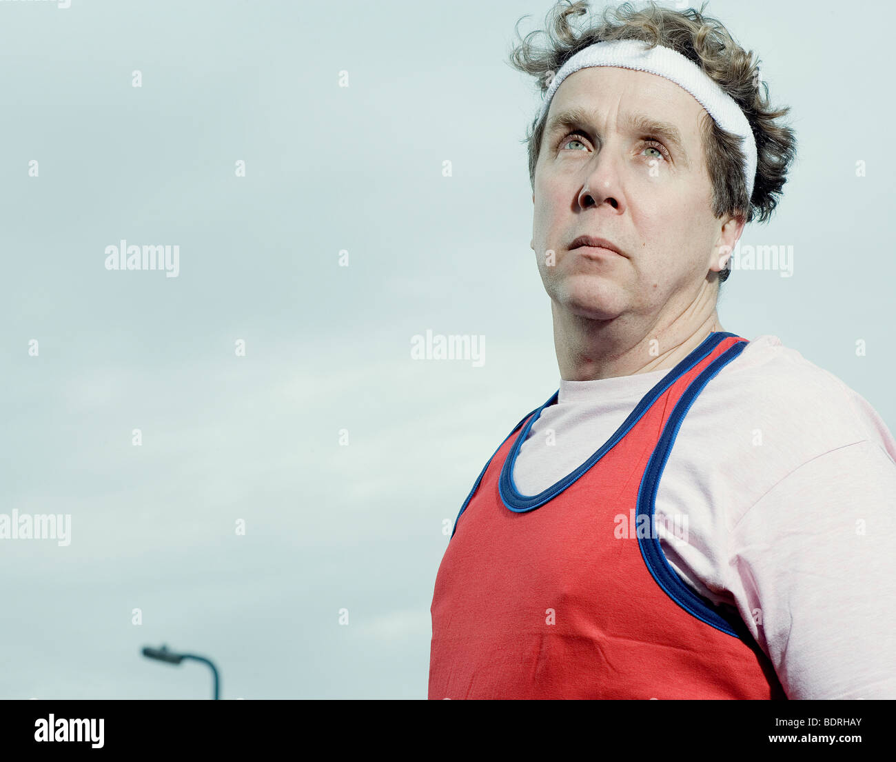 Man dress in jogging gear looking a bit daft but in a heroic pose - Stock Image