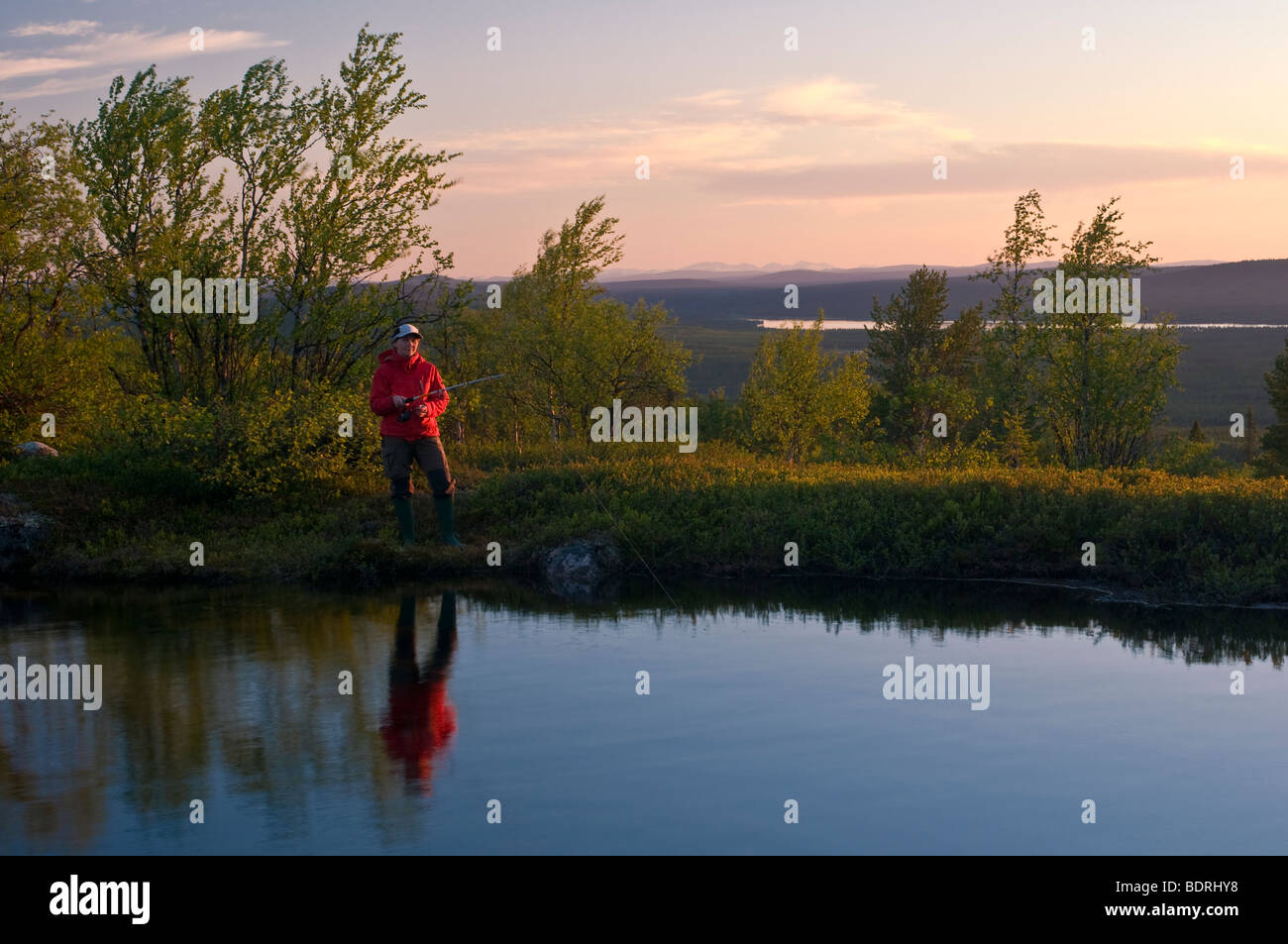 female angler at a mountain lake in lapland at midnight sun, sweden Stock Photo