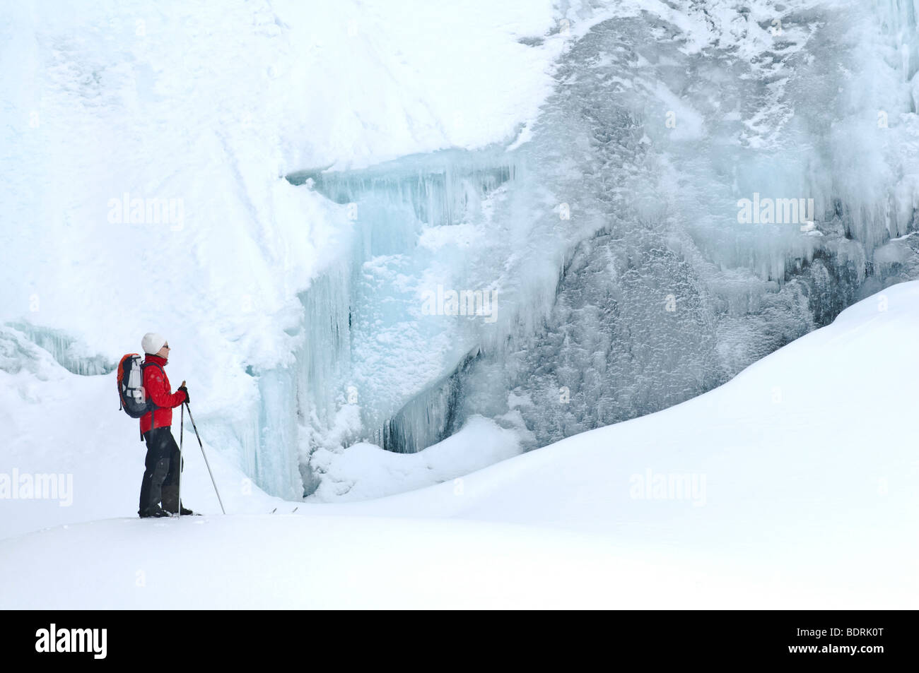 female skier in front of a frozen waterfall in padjelanta national park, swedish lapland - Stock Image
