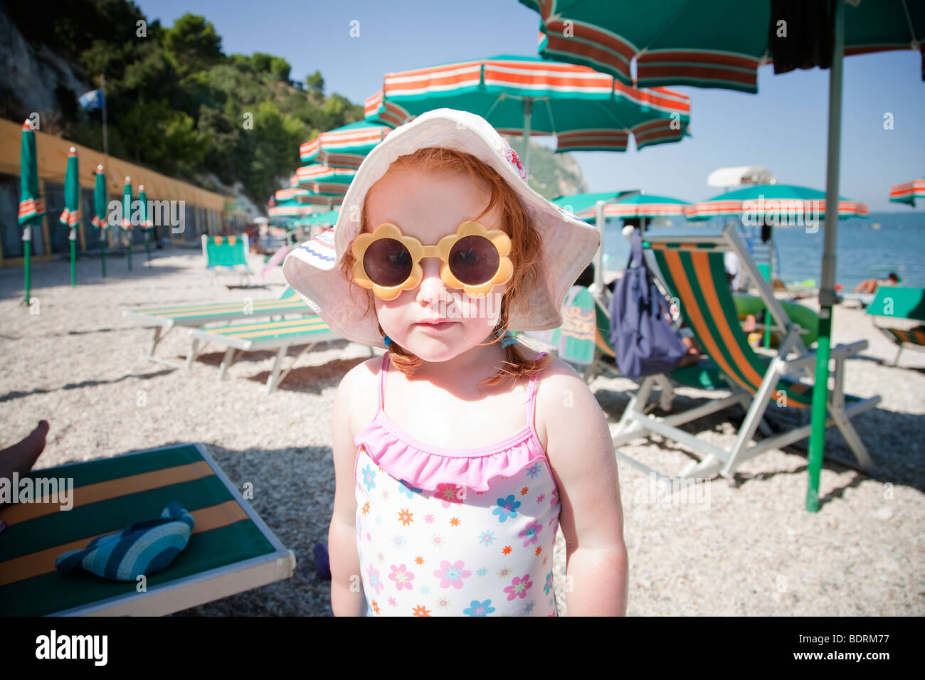 Fair skinned redhead girl on the beach wearing sunglasses and a sunhat - Stock Image